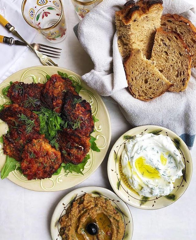 """🇬🇷🌱@cardamom_and_dill are launching a brand new Friday night dining concept! 🌱🇬🇷 Judging by her lunch menus and supper clubs over the past 6 months, this will no doubt be equally amazing. Here's Kiki's wonderfully eloquent description of proceedings: """"My Greek-inspired taverna-style supper night, Friday 3rd May, from 6pm until 8pm The first of my taverna-style suppers is inspired by various dishes I've enjoyed amongst the Greek Islands. My menu will include the following: A slice of my sumptuous feta and spinach spanakopita, my gorgeous Santorini tomato keftedes with halloumi and wild oregano (pictured), Dimitri's zing-fresh Greek salad A deeply umami melitzanosalata – a roasted aubergine dip (pictured) and my Greek Island tzatziki with cucumber, dill and mint (pictured). The price is £15 for my classic 'Cardamom and Dill Tasting Plate' comprised of a little bit of everything with some freshly baked sourdough on the side. Please call me to book your table."""" See you Friday!⚡️"""