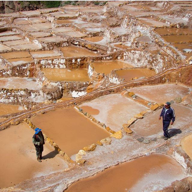 Two salt miners chatting away at the Salineras de Maras, salt mines close to Cusco.  There is a lot of salt in the mountains around here. Because the ground water is warm the salt dissolves and can be mined like displayed here. In the rainy season the baths look like this, in de dry season all the water evaporates and the salt can be taken out.  #travels #salt #culture #salineras #cusco #todolistmagazine #natgeotravel #work #ontheroad #Peru #beauty #thetravelwoman