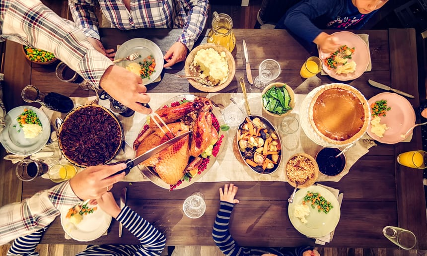 A family having a traditional holiday dinner with stuffed turkey, mashed potatoes, cranberry sauce, vegetables, pumpkin and pecan pie. Photograph: GMVozd/Getty Images