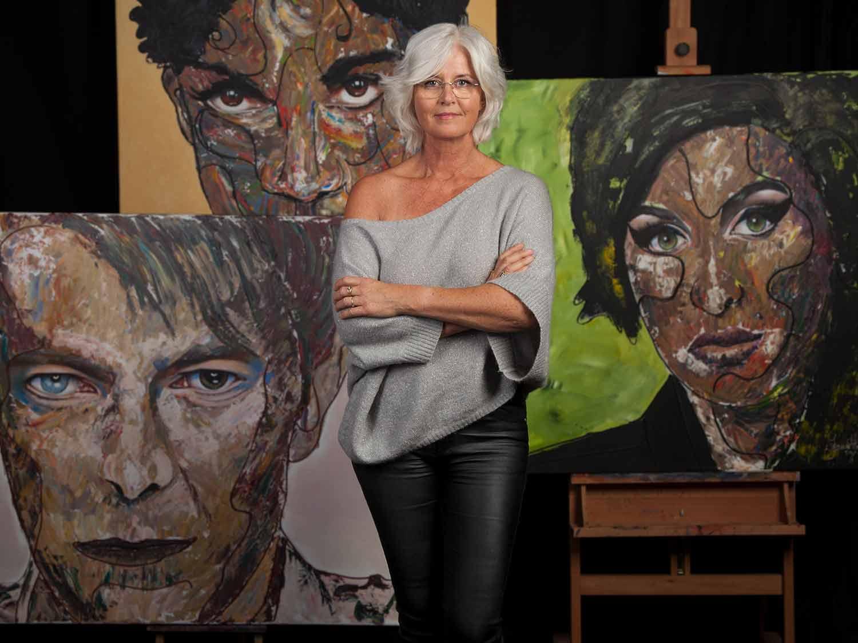 Kunstenares Jeannette van der Vliet in haar atelier, poserend voor een aantal van haar portretschilderijen