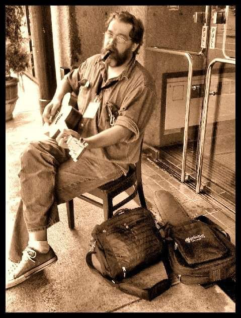 Sitting on the street in Nashville, smoking a cigar and picking. 2008 or so