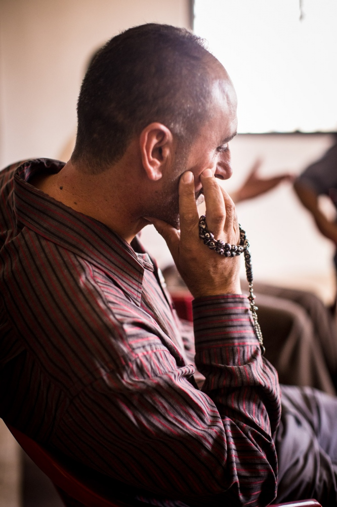 An Iraqi man sits in a men's group therapy session at the Collateral Repair Project community center in Amman, Jordan. The men pass around a string of prayer beads and take turns sharing whatever is on their mind, giving them an outlet to deal with trauma they've witnessed, or the frustrations of not being able to work in Jordan.