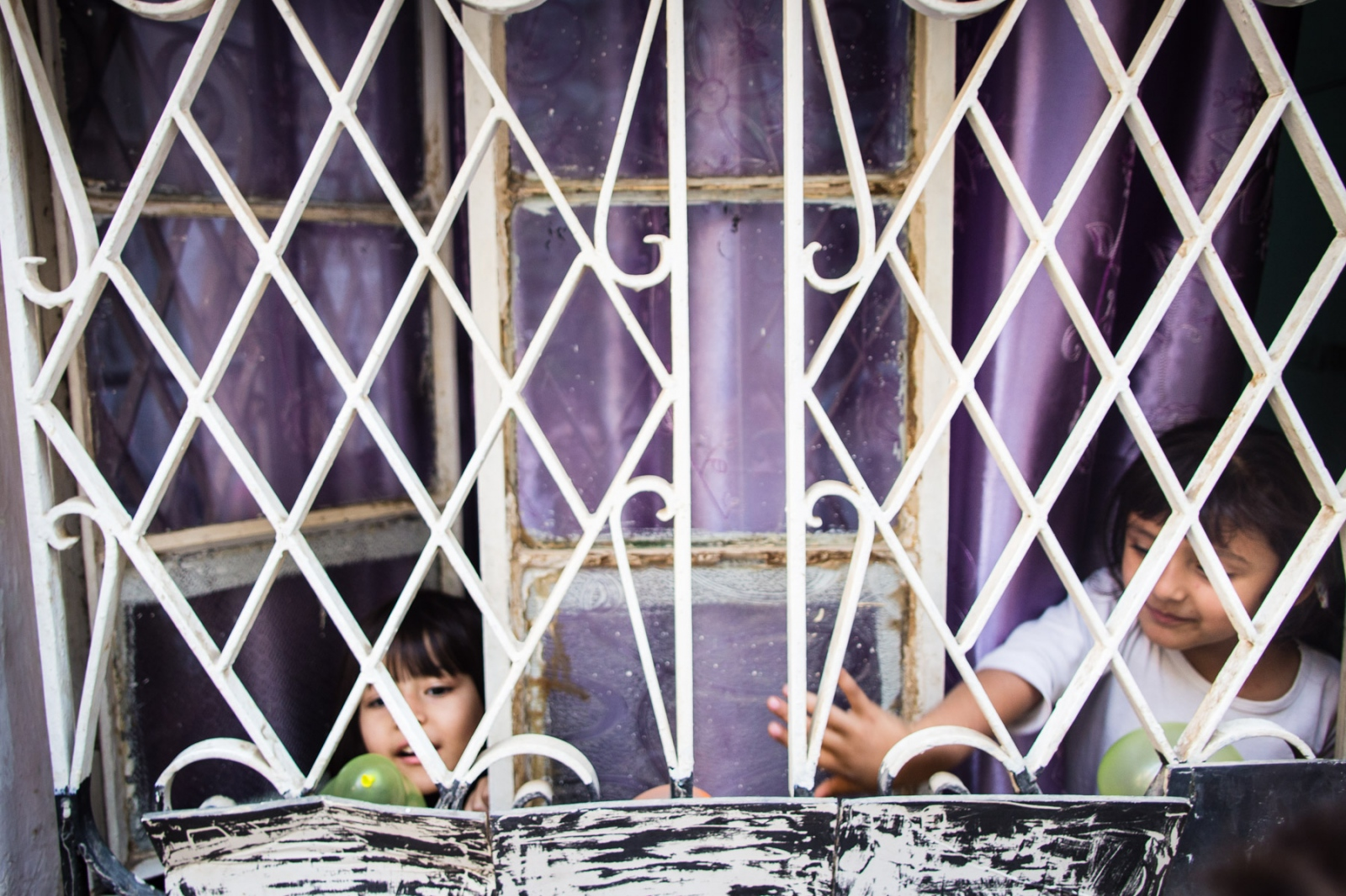 Two young Iraqi girls play with balloons in the window of Collateral Repair Project's community center in the Hashemi Shmali neighborhood of Amman, Jordan. The center provides educational activities for children as well as vocational training and language courses for adults.