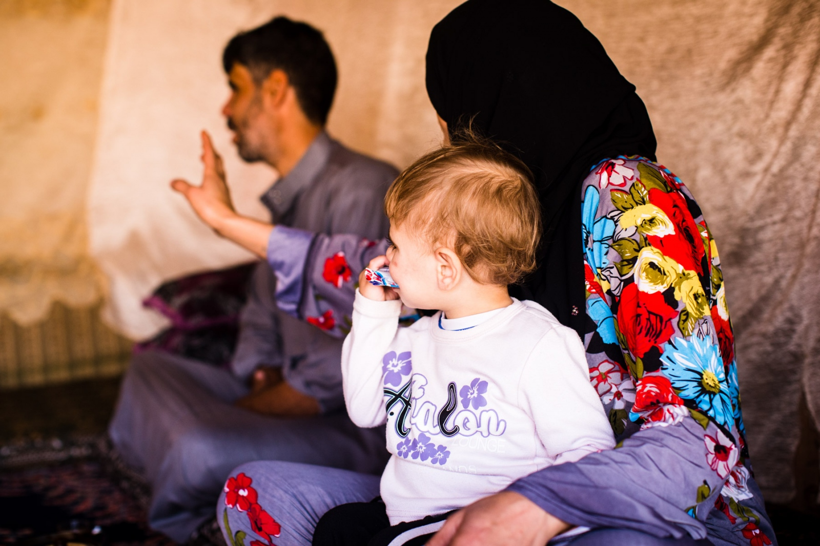 Dahham Al Obeid, 37, and his wife Kafaa, 32, sit with their son Sultan at home in Mafraq, Jordan, on Nov. 4, 2016. The Al Obeid family fled Homs, Syria five years ago, and since then have been living on their own in a tent just outside Zaatari Refugee Camp in Mafraq, Jordan. The family receives 50 Jordanian dinars in food vouchers, and receives little other assistance.