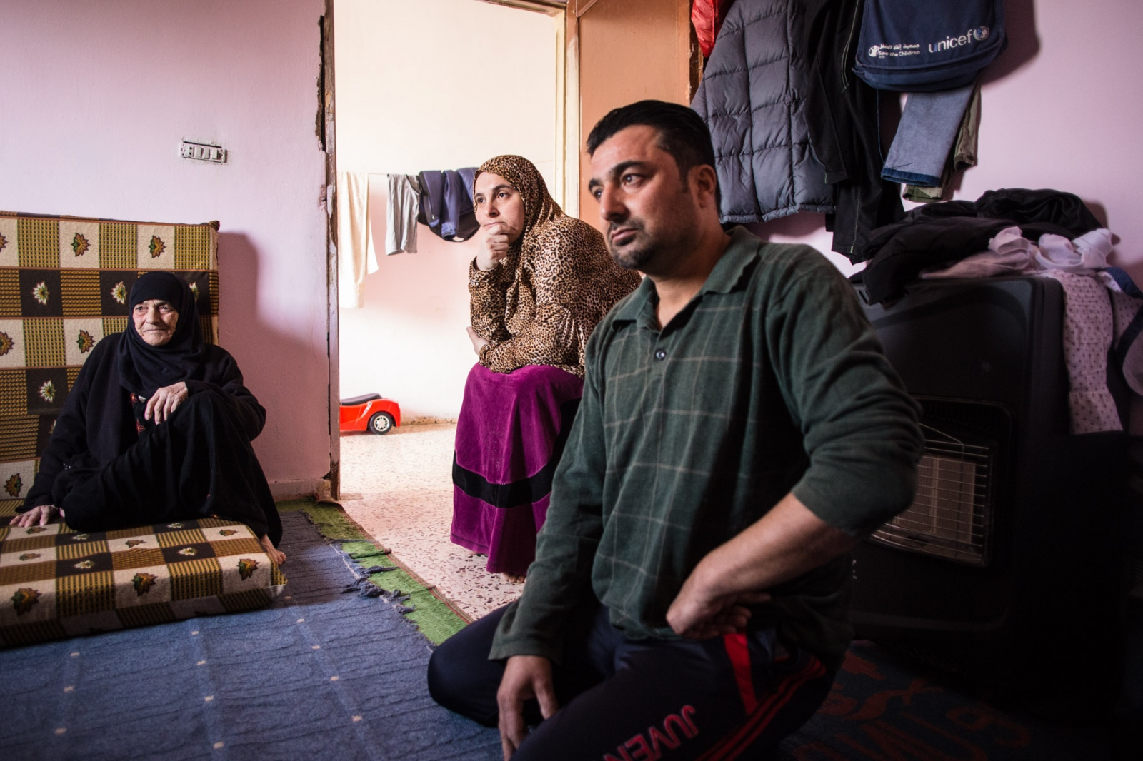 Ahmed Jansis, 41, sits with his wife Um Mohammed, mother, and son Hamzah at home in Mafraq, Jordan, on Nov. 4, 2016. The family came from Aleppo, where Um Mohammed worked as an English teacher, and now both parents do odd jobs to earn a basic income for the family.
