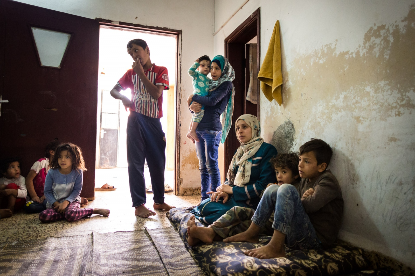 Abu Mohammed's family, originally from Syria, sits at home in Mafraq, Jordan, on Nov. 4, 2016. This house has about 15 people living in two rooms with his second wife; he has another household with his first wife, also with about 15 people.