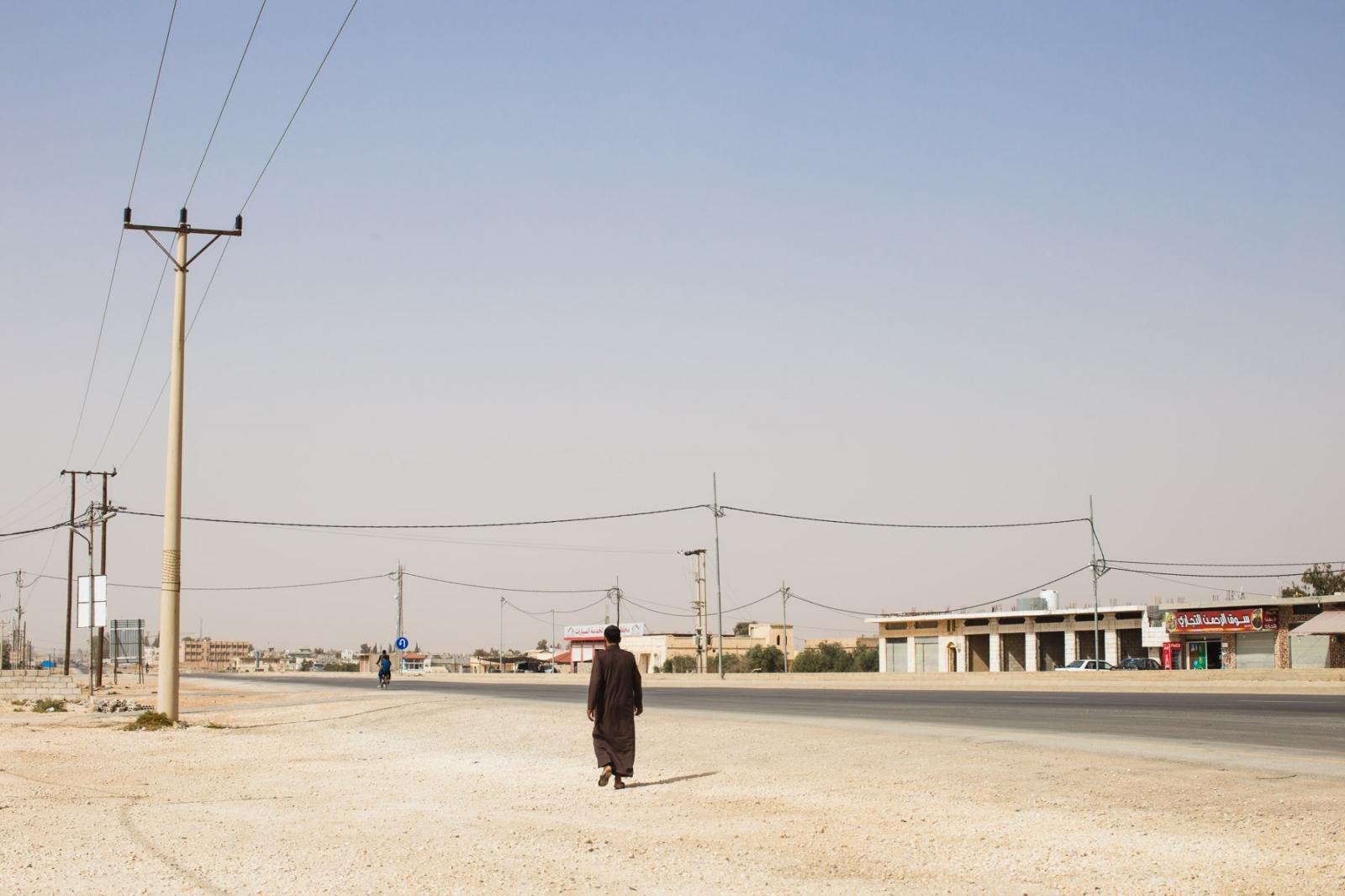 A man walks along the desert stretch of road outside of Za'atari Refugee Camp in northern Jordan.