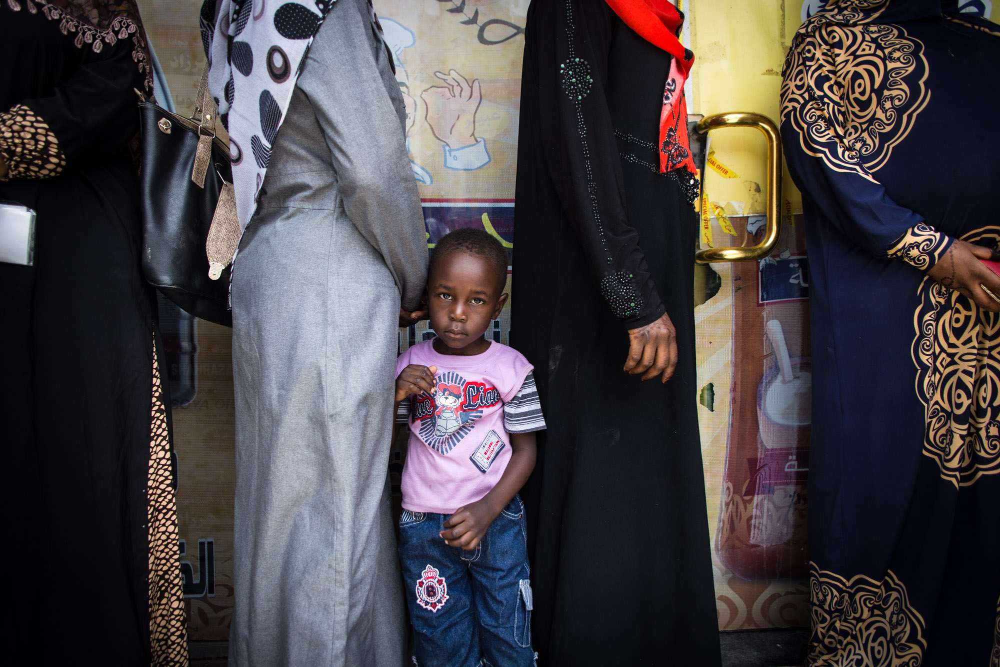 A young Sudanese boy stands in line with his mother and other women to buy food from a supermarket with a food voucher they receive from local NGO Collateral Repair Project in Amman, Jordan. Refugees living outside official camps - Sudanese refugees in particular - receive little aid and often feel neglected by the UN and international NGOs.