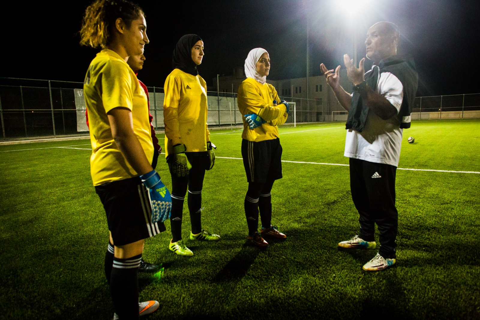 Rand al-Bustanji (2nd left) and her teammates listen to their coach at a practice session at Sports City in Amman, Jordan.