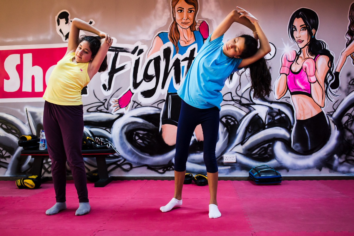 Sana Kayyali and Reem Habib stretch and do yoga poses in between kicking and punching exercises during a self defense class at She Fighter in Amman, Jordan, on August 21, 2015. The She Fighter studio was founded by Lina Khalifeh, and offers self defense classes to young women to protect against harassment.