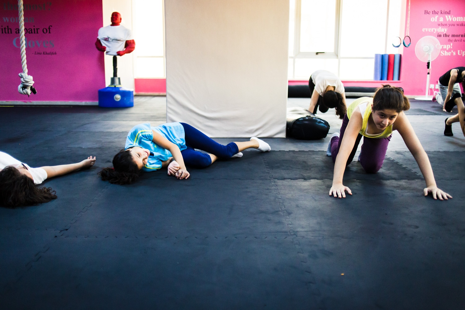 Reem Habib collapses on the floor, laughing, after holding the plank position during a self defense class in Amman, Jordan, on August 21, 2015. The She Fighter studio was founded by Lina Khalifeh, and offers self defense classes to young women to protect against harassment.