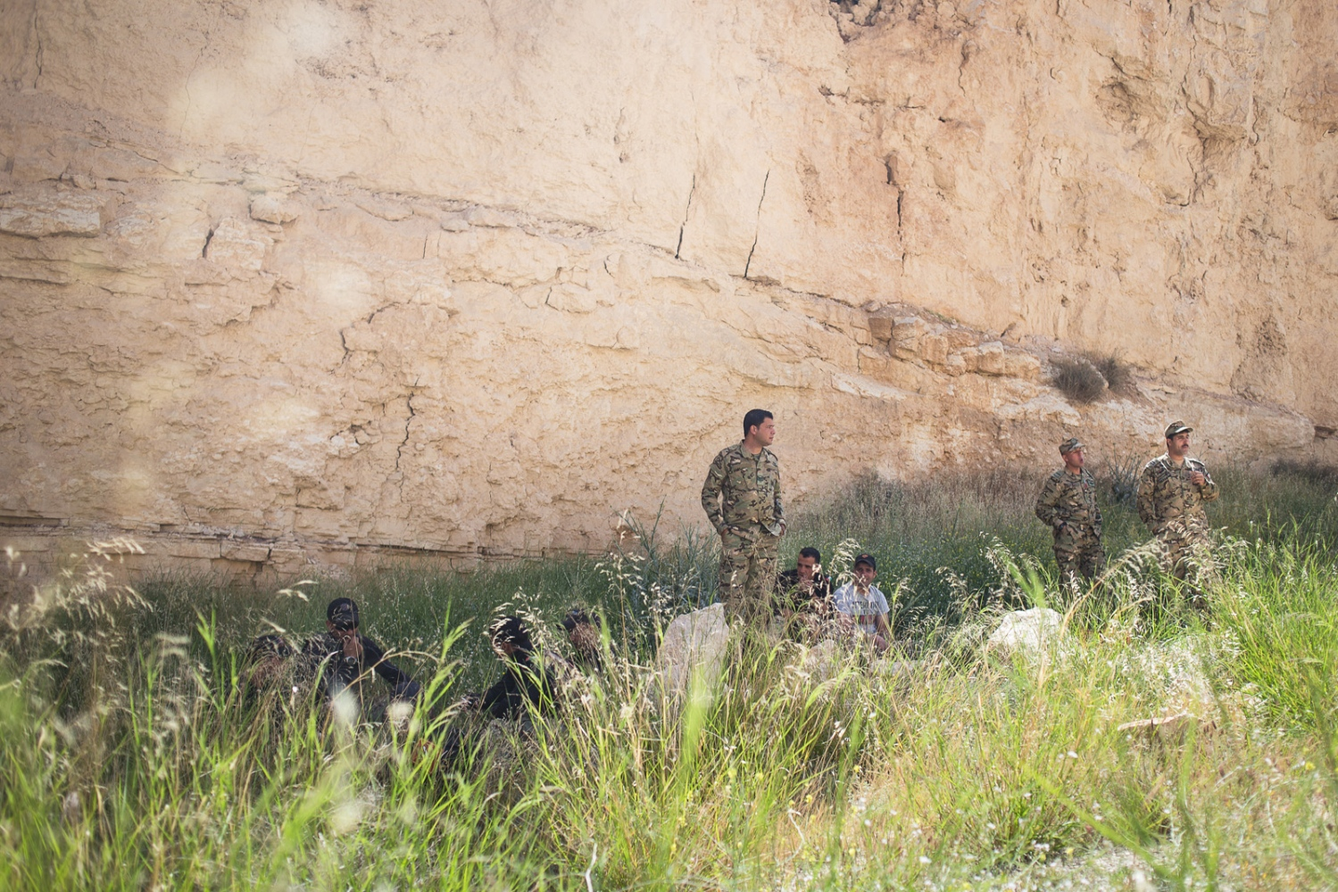 "The Jordanian team rests in the shade of a sandstone cliff before the ""urban assault"" event at the Warrior Competition on April 21, 2015. In this event, soldiers must rush over a dirt verge, storm a building in a mock city, rescue a hostage and fire at targets in the distance."