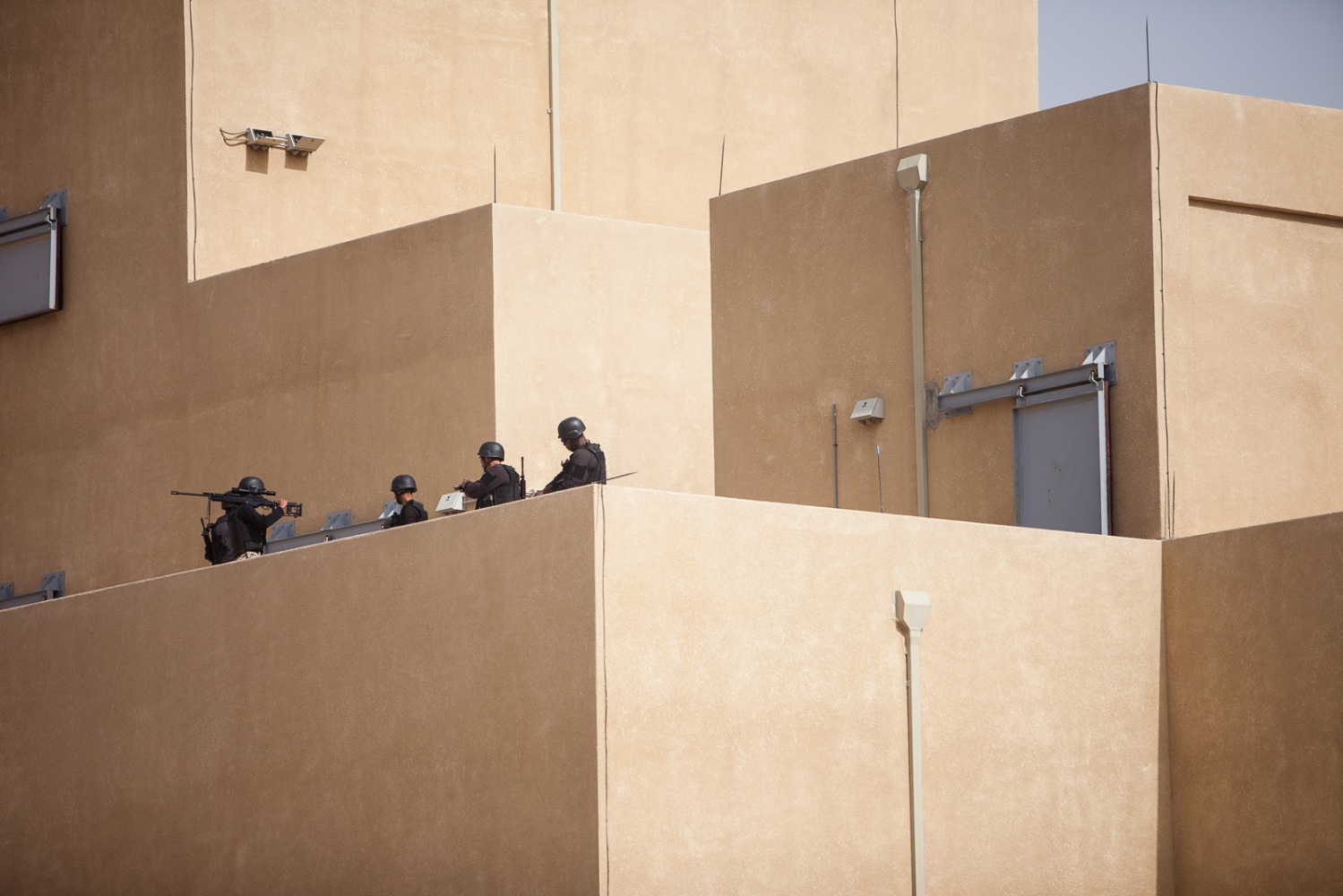 "Soldiers wait for instructions atop a tower during the ""Urban Assault"" event on April 20, 2015, during the seventh annual Warrior Competition near Amman, Jordan. The center, which spans 25 acres of a blasted-out desert canyon, is a state-of-the-art training facility complete with mock cityscapes, villages, and grounded aircraft. The exercises are all performed with live ammunition."