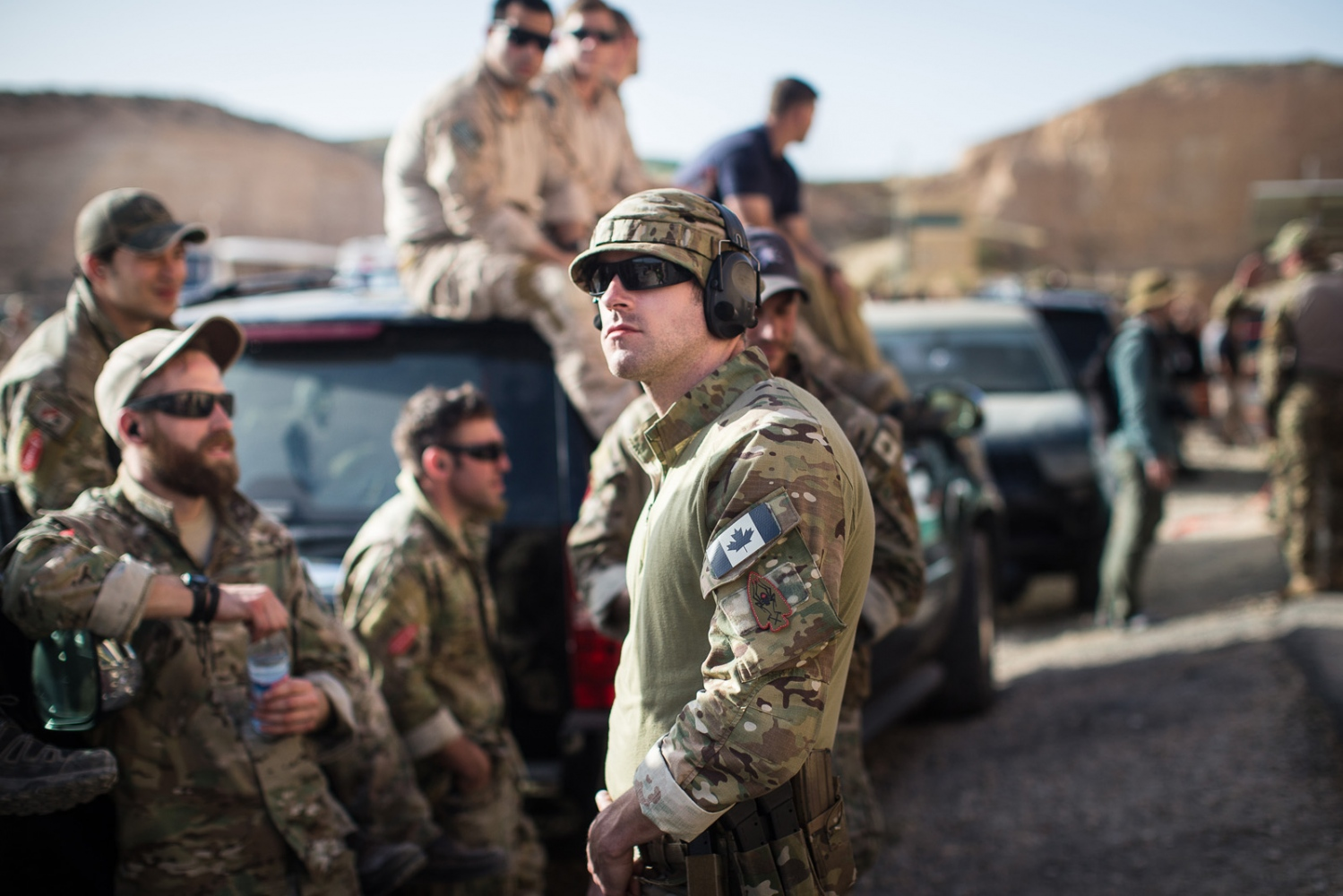 "Members of the American and Canadian teams cheer together and watch the remaining teams compete in the ""Top Gun"" event at the seventh annual Warrior Competition at the King Abdullah II Special Operations Training Center near Amman, Jordan on April 19, 2015. Jordan and the United States were finalists in the event, with Jordan ultimately coming in first place."