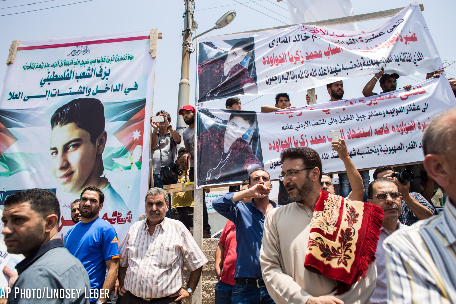 Placards are seen at the funeral of Mohammed al-Jawawdeh, a 17-year-old Jordanian, who was killed on Sunday evening by an Israeli security guard who said he was attacked by him with a screwdriver, on Tuesday, July 25, 2017 in Amman, Jordan. (AP Photo/Lindsey Leger)