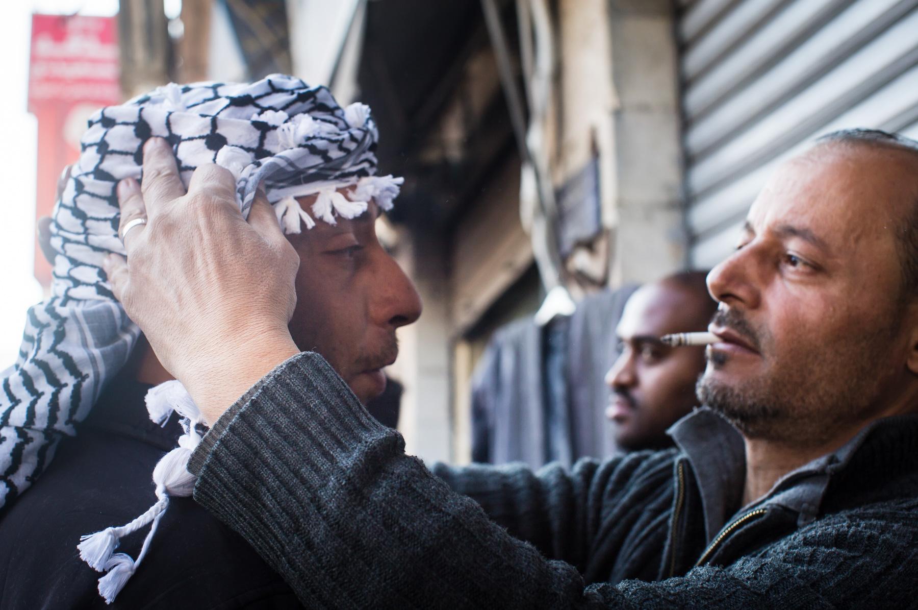 A shopkeeper helps a man adjust his Palestinian keffiyah scarf during a demonstration in downtown Amman, Jordan, on Dec. 8, 2017.