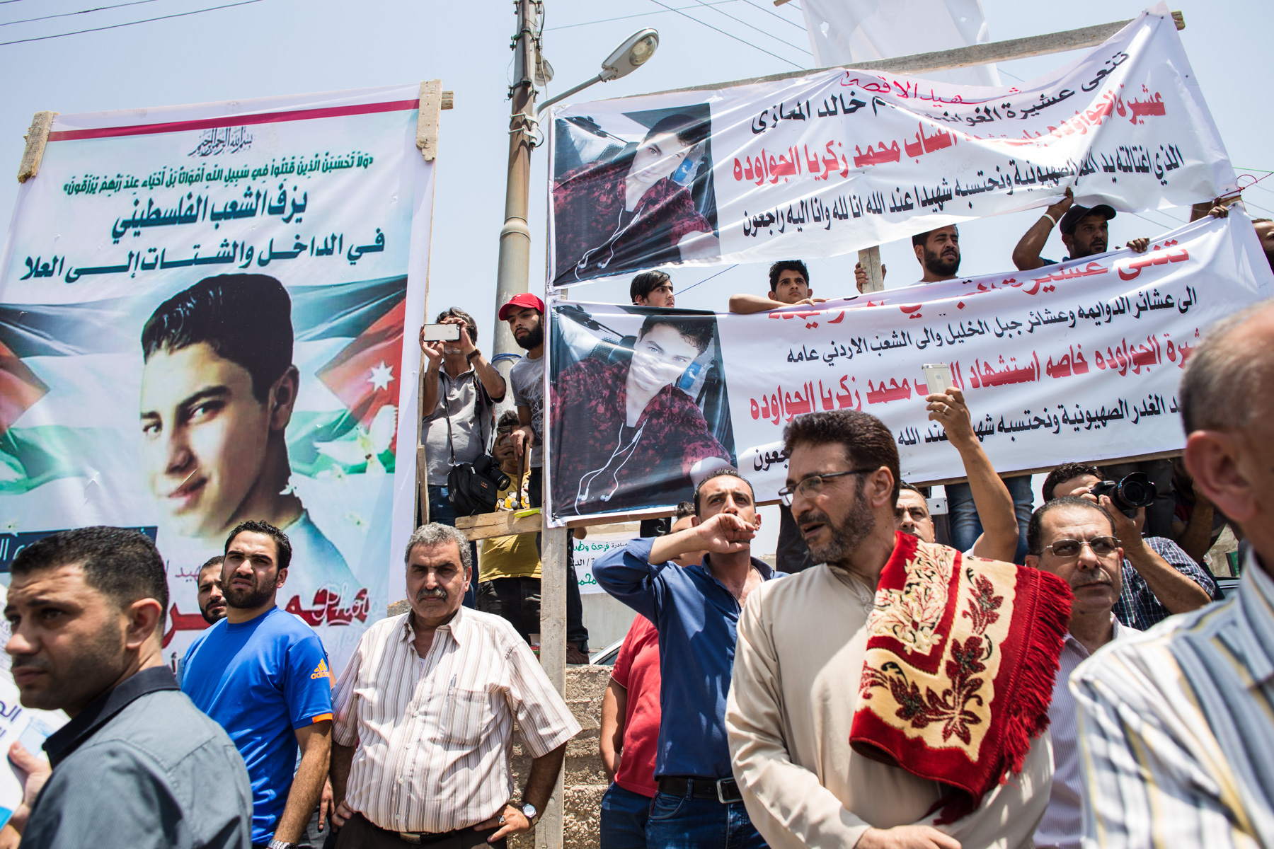 Placards are seen at the funeral of Mohammed al-Jawawdeh, a 17-year-old Jordanian, who was killed on Sunday evening by an Israeli security guard who said he was attacked by him with a screwsdriver, on Tuesday, July 25, 2017 in Amman, Jordan.
