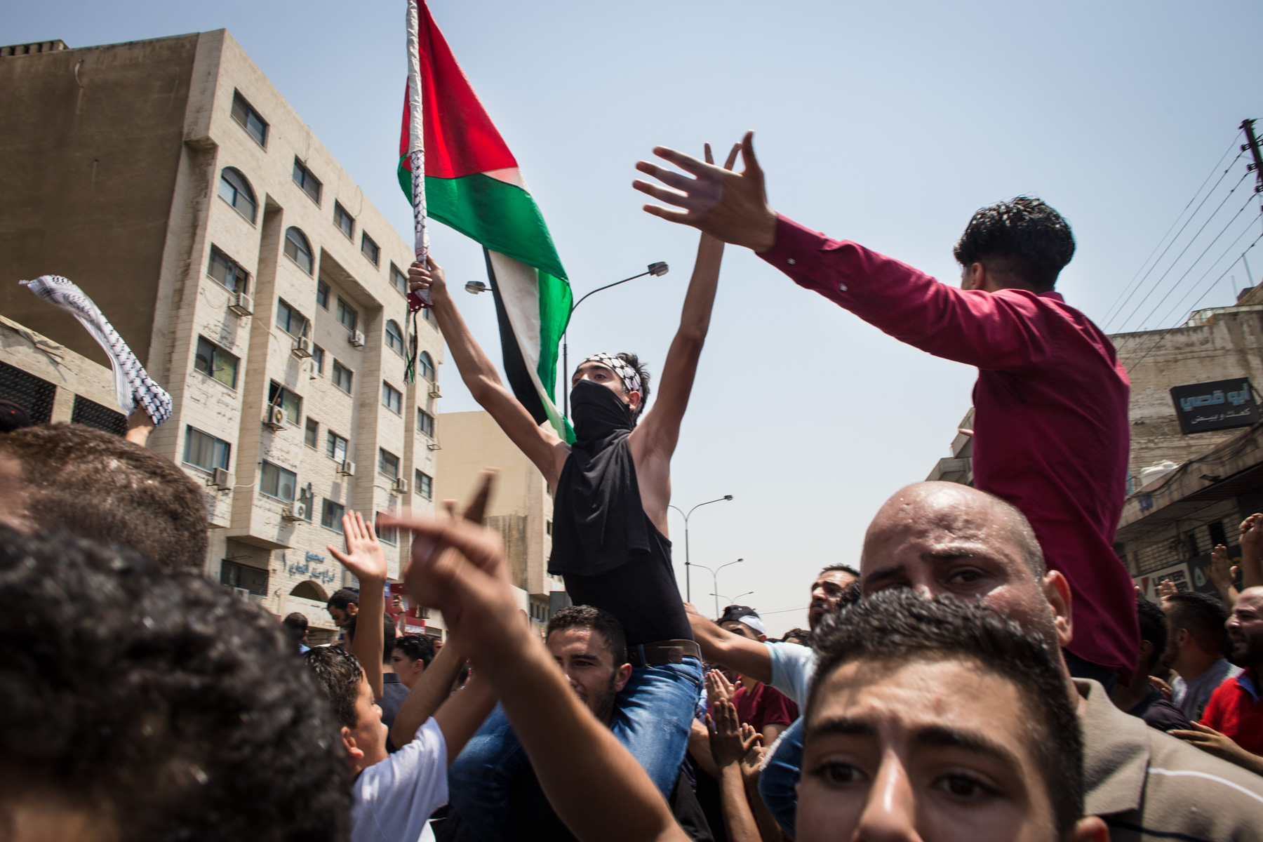 Mourners march, waving the Palestinian flag, at the funeral of Mohammed al-Jawawdeh, a 17-year-old Jordanian, who was killed on Sunday evening by an Israeli security guard who said he was attacked by him with a screwsdriver, on Tuesday, July 25, 2017 in Amman, Jordan.