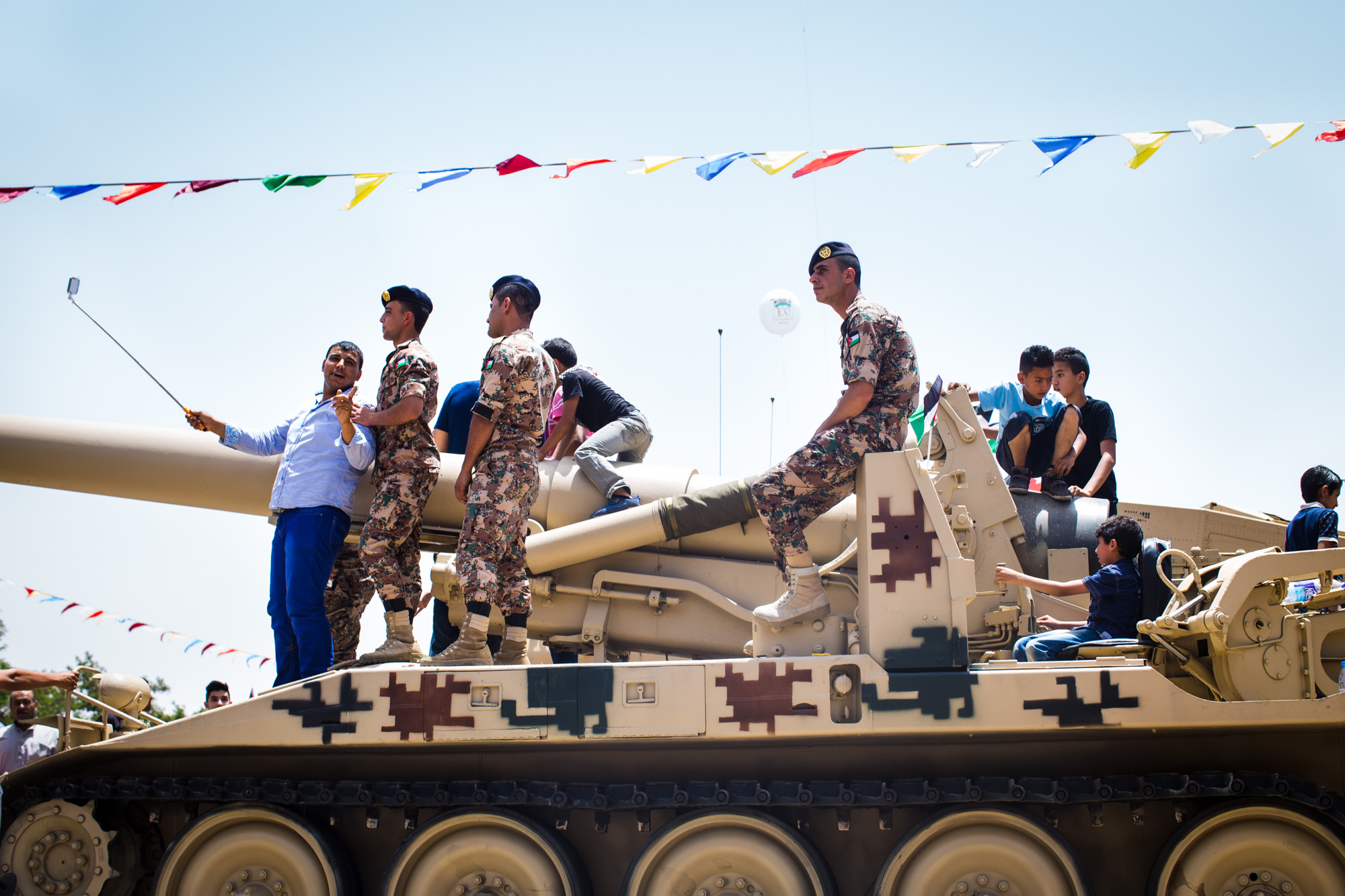 People pose for a selfie with Jordanian soldiers on top of a tank at a festival celebrating the centennial of the Great Arab Revolt in Amman, Jordan on June 3, 2016.
