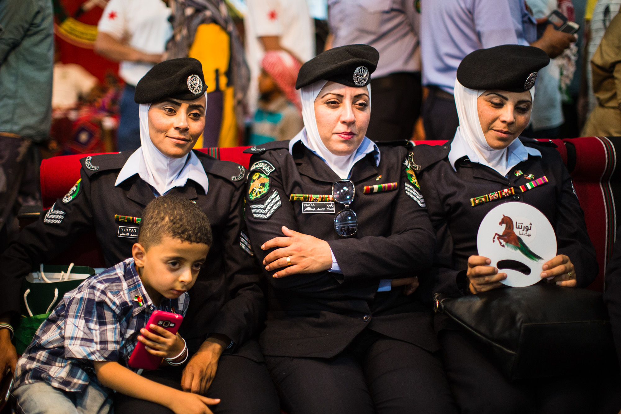 Jordanian women police officers sit with their kids at a festival marking the 100th anniversary of the Great Arab Revolt in Amman, Jordan, on June 3, 2016.