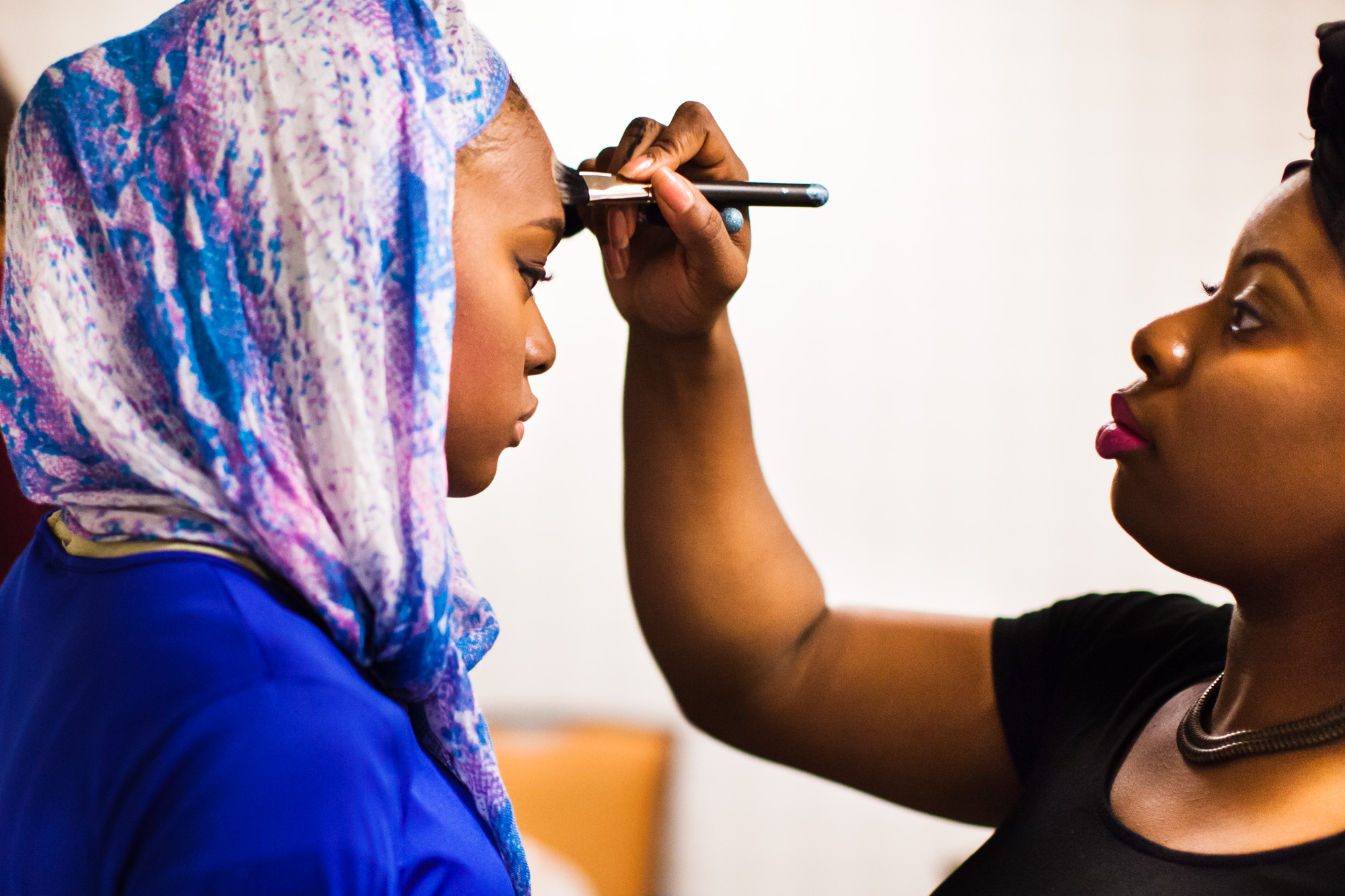 Jalila Ahmad gets her makeup done by Christelle Francois. Reaching All HIV+ Muslims in America (RAHMA) hosted a fashion show in Washington, DC on Aug. 16, 2014. The clothing and accessories are all made by Muslim women designers from around the US. They specialize in creating modest fashion that complies with Islamic tradition.