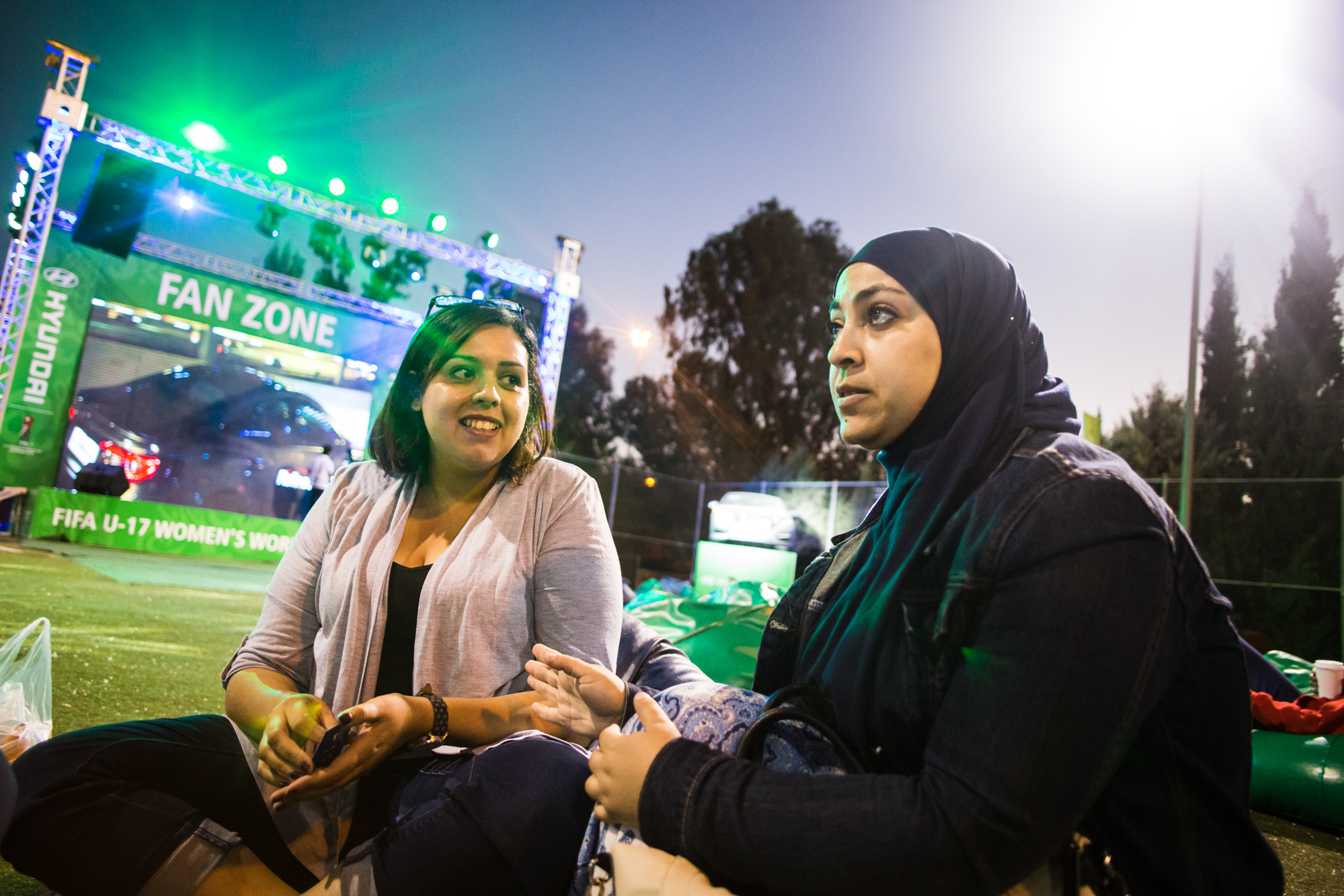 The fans: Esra'a Abed Alqader (left) and Fadwa Abushaikha, two volunteers for  the U17 women's world cup in Jordan, sit together and watch a match between Spain and Japan at the Fan Zone in King Abdullah Park in Amman, Jordan, on Oct. 17, 2016.