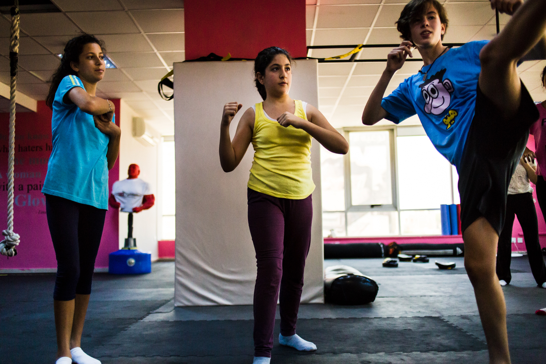 Reem Habib, Sana Kayyali, and Selina Hajarat practice their moves in front of a mirror during class at She Fighter in Amman, Jordan, on August 21, 2015. The She Fighter studio was founded by Lina Khalifeh, and offers self defense classes to young women to protect against harrassment.