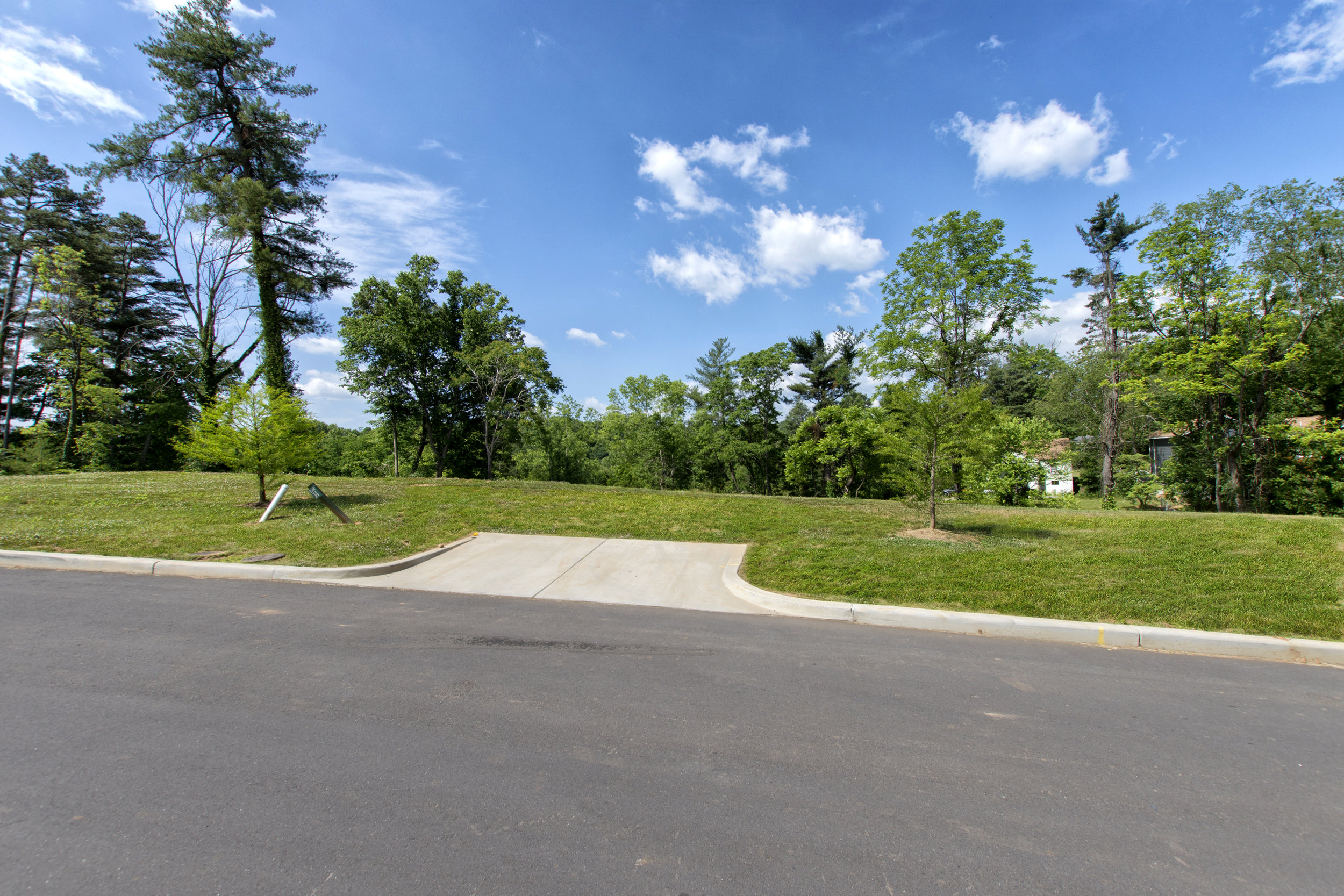 LOT 14 - 0.23 acres - $125K - Lot 14 features a level entrance with the land sloping downward toward the back of the lot, ideal for a home with a walkout basement. Sunset views possible from the back of your home. -