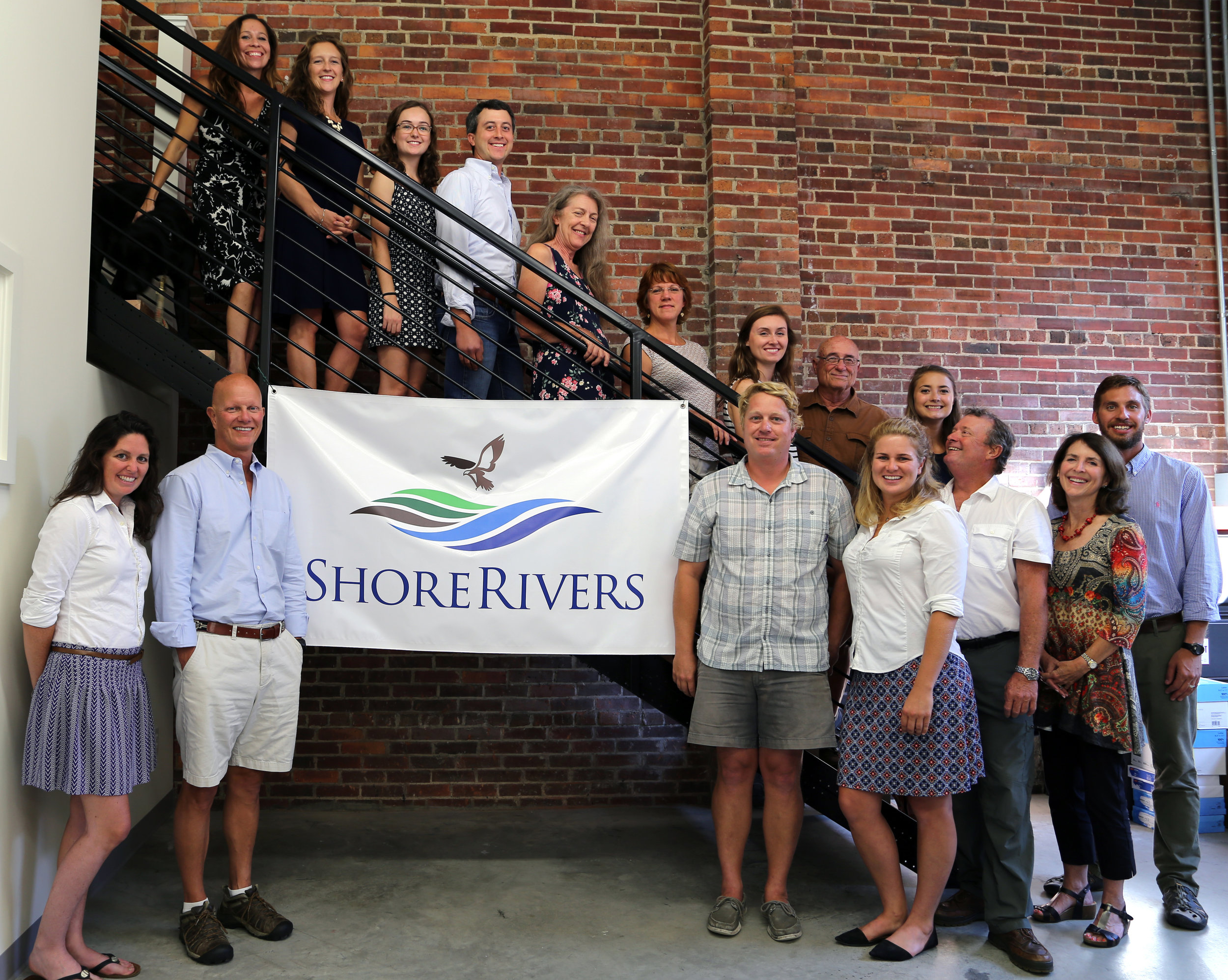 ShoreRivers staff celebrate their new Easton headquarters following the merger of three environmental organizations in January 2018. Pictured are (front row, left to right) Elle Bassett, Jeff Horstman, Tim Trumbauer, Suzanne Sullivan, Tim Junkin, Kristin Junkin, Matt Pluta; (back row, left to right) Kristan Droter, Isabel Hardesty, Laura Wood, Tim Rosen, Ann Frock, Kim Righi, Emily Harris, Emmett Duke, and Rebecca Murphy.