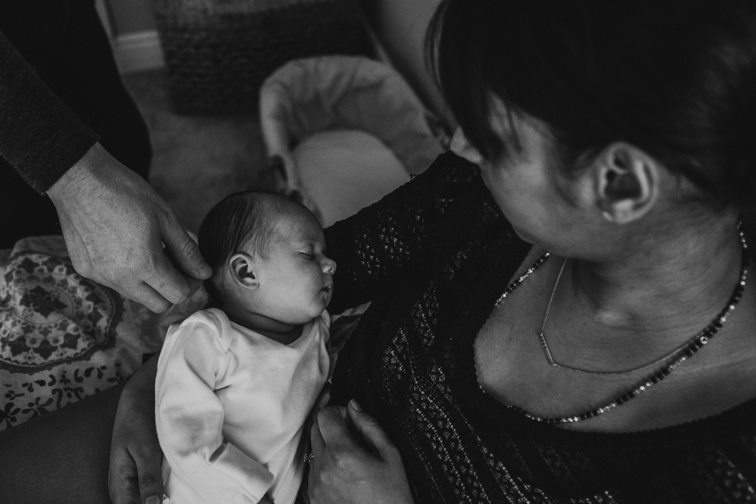 Documentary newborn photography session captures mother and father admiring their baby at their home in Chesterfield, Derbyshire.