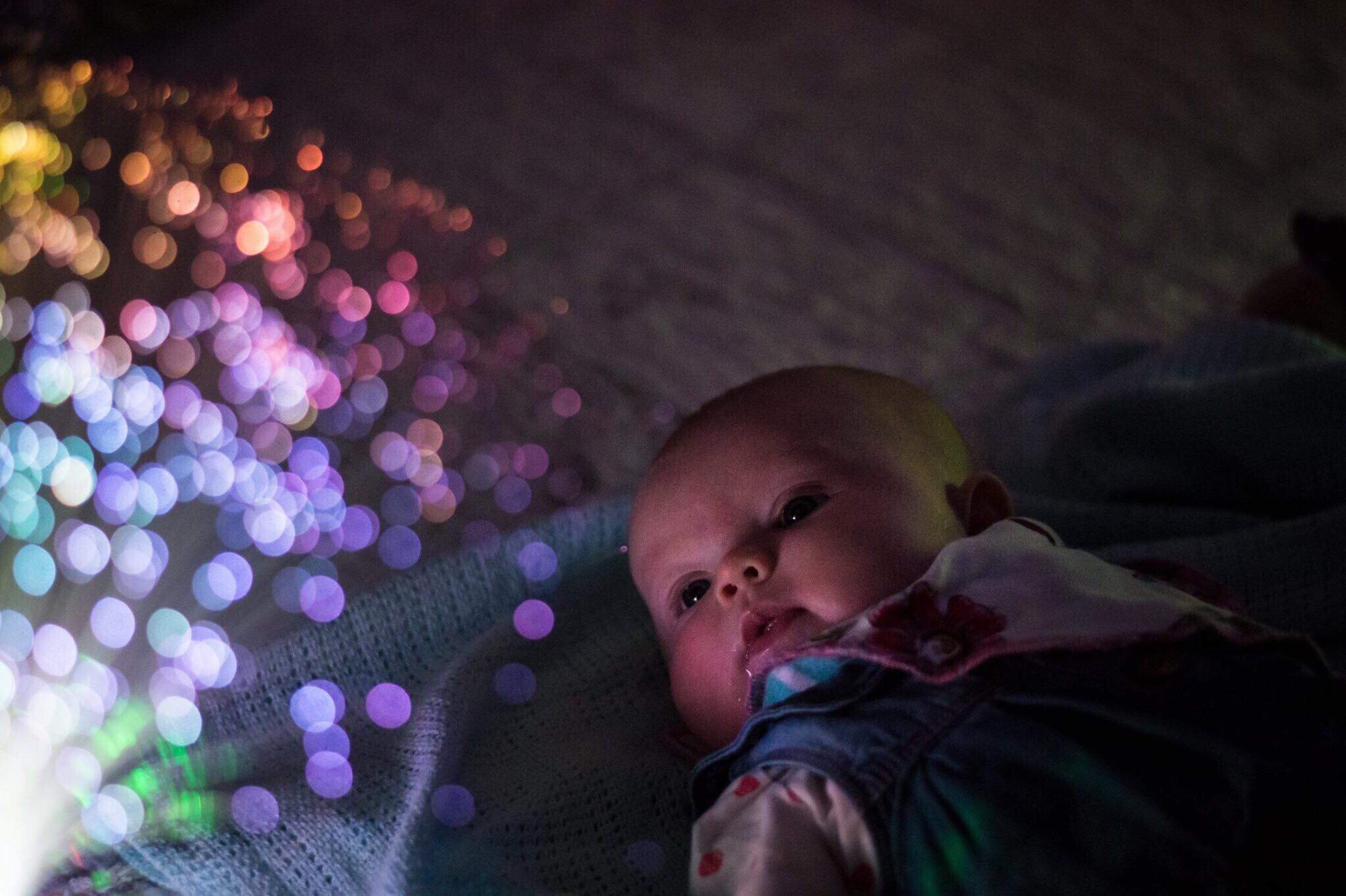 A small infant studies the colourful lights at Little Glow in Ravenshead.