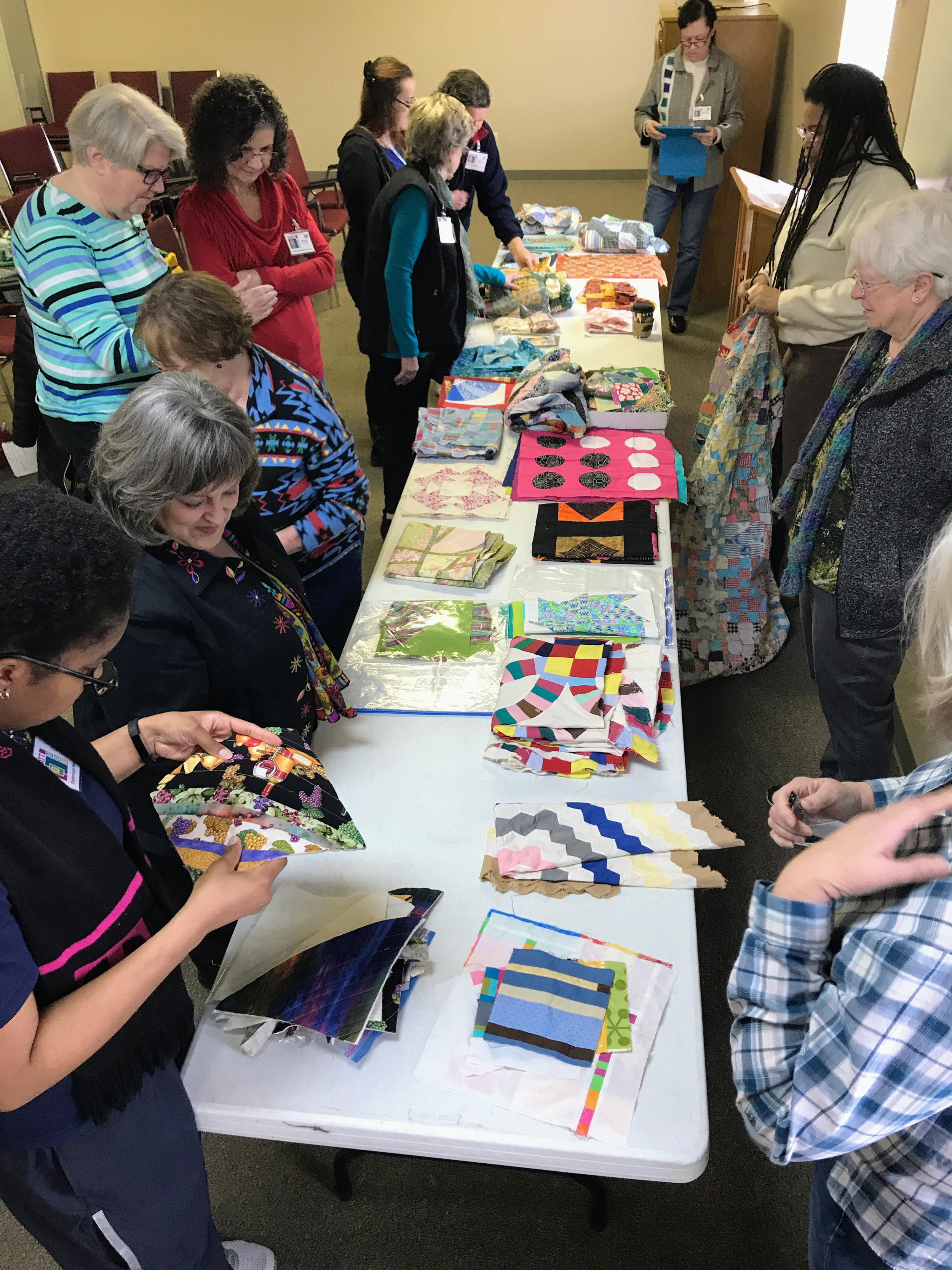 Challenge participants examine the UFOs, orphan blocks, and quilt tops up for grabs.
