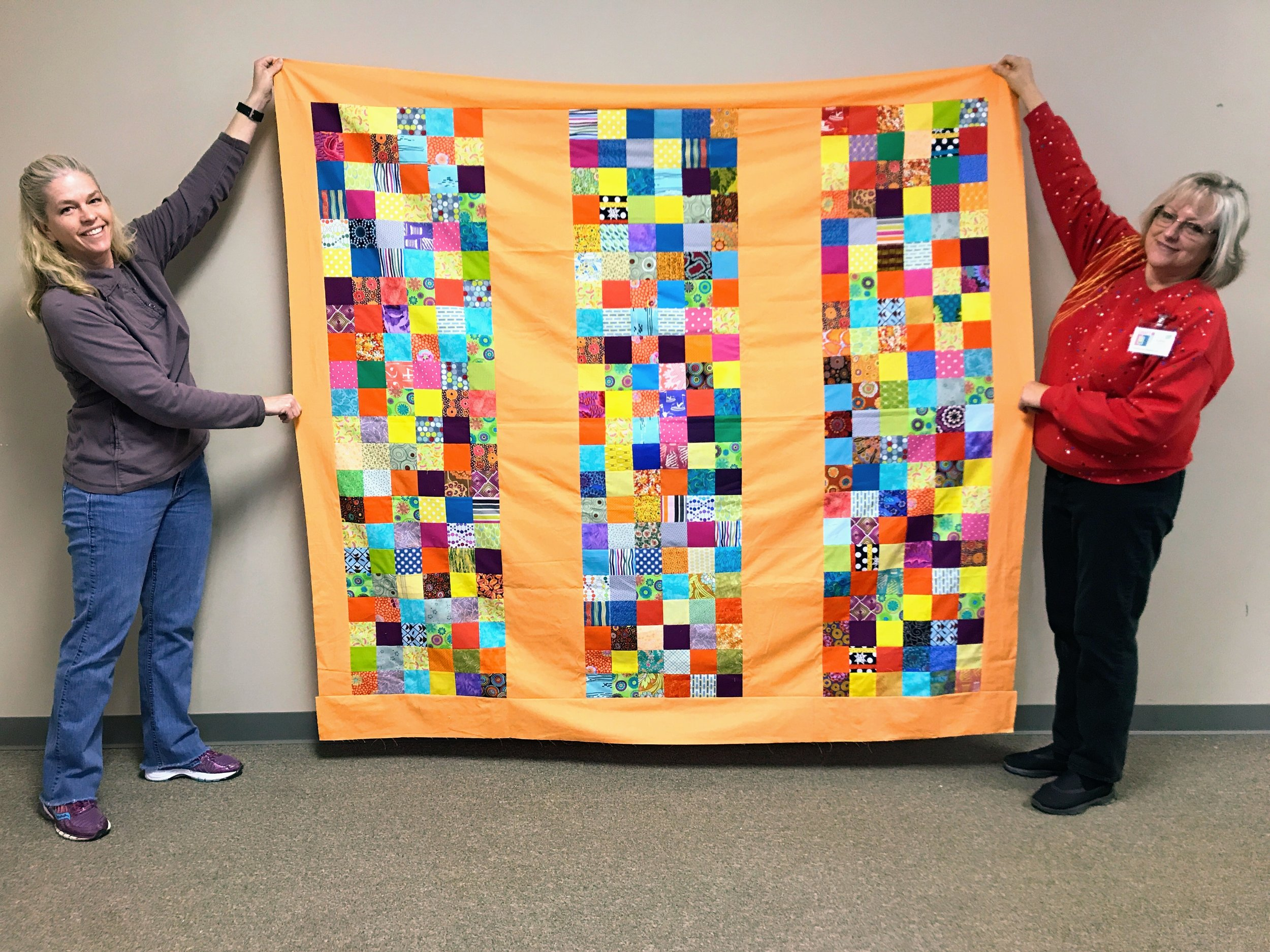 Sara (left) and Karen (right) hold the quilt top Sara completed for a 2018 Habitat homeowner.