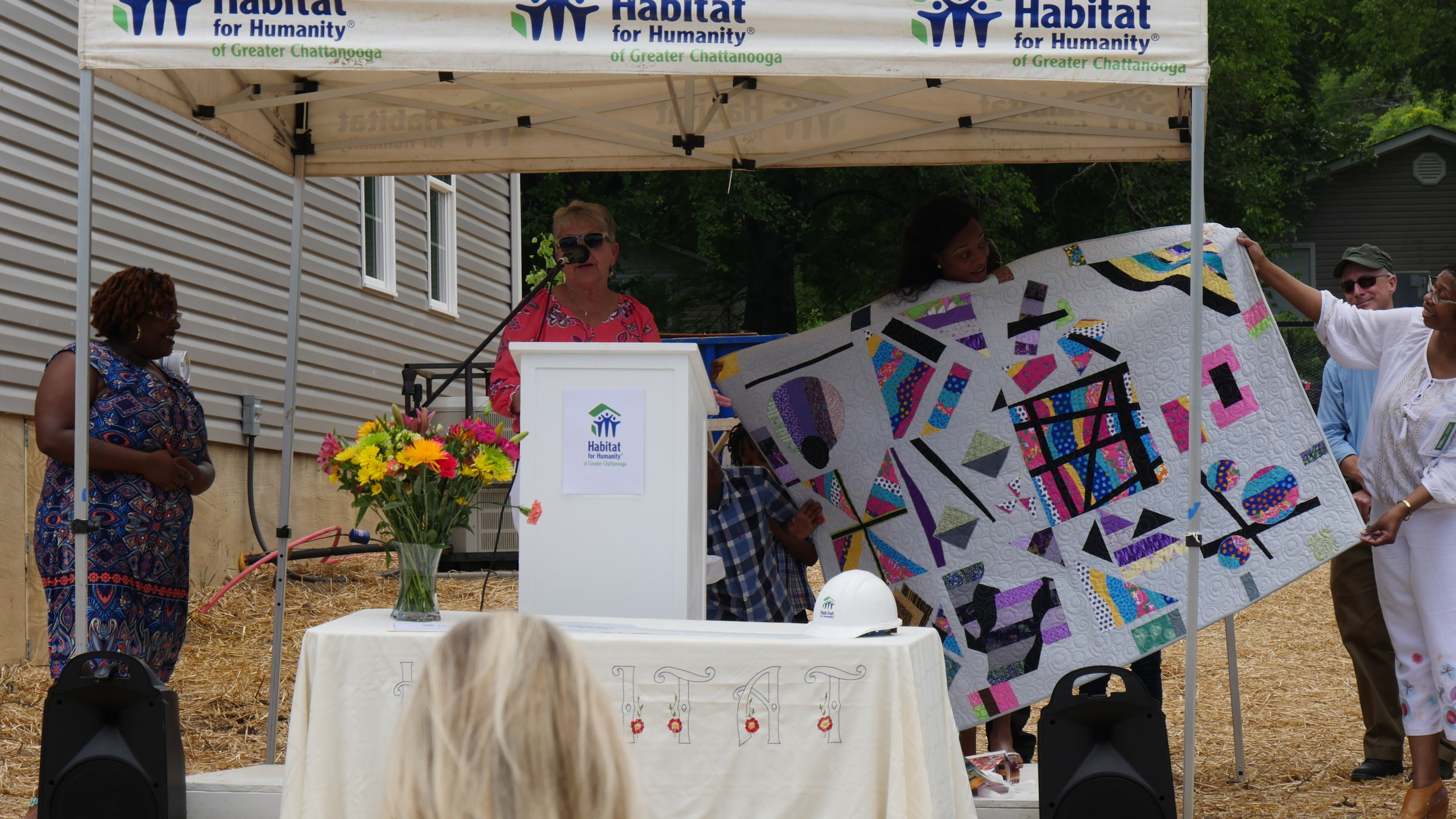 Sandi Suggs (behind podium) presents Ashley (center) with her quilt.Photo courtesy of Habitat for Humanity of Greater Chattanooga.
