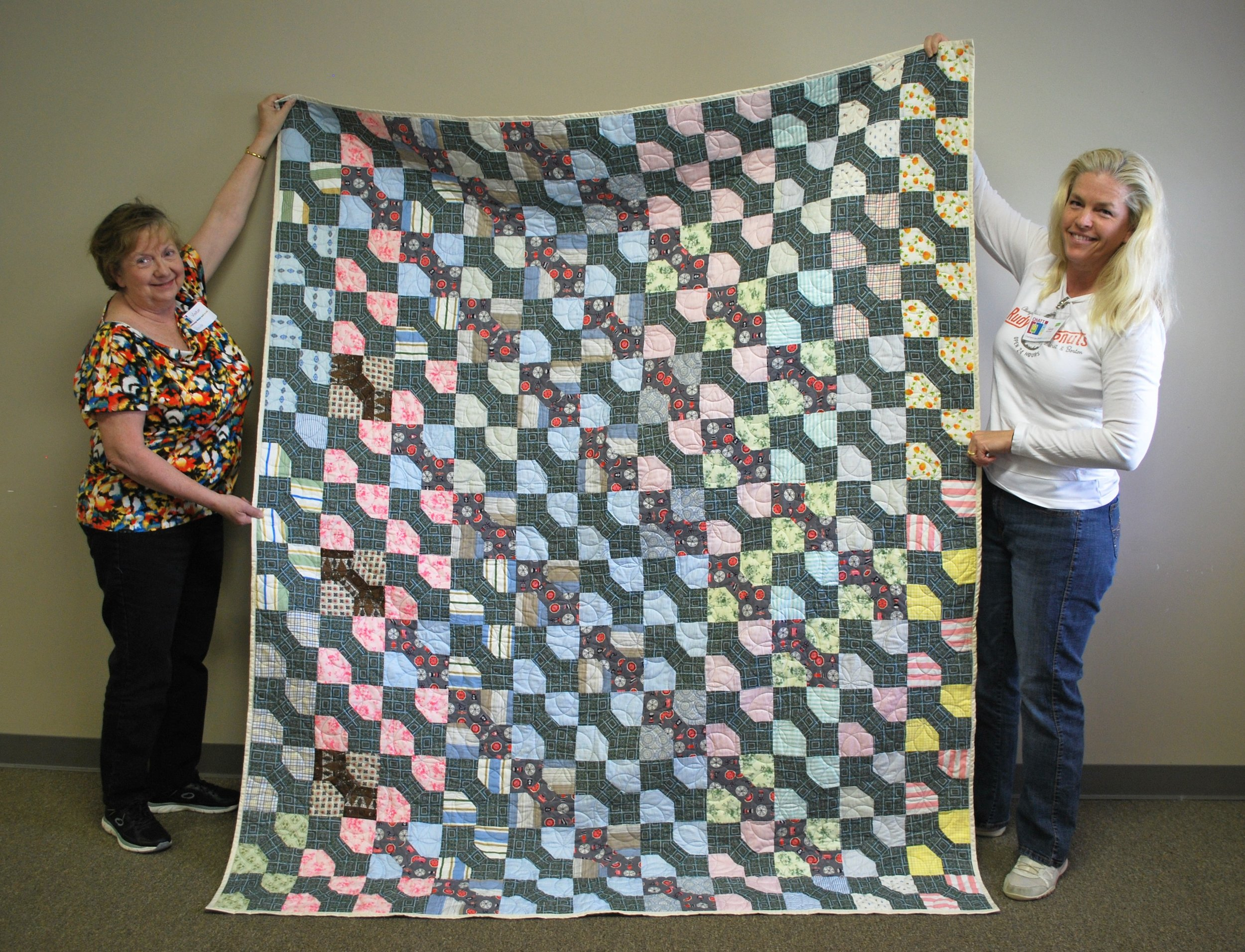 Rhonda Fulghum (left) quilted this top donated by Catherine Price. Sara Bradshaw (right) will send it to Operation Underground Railroad.
