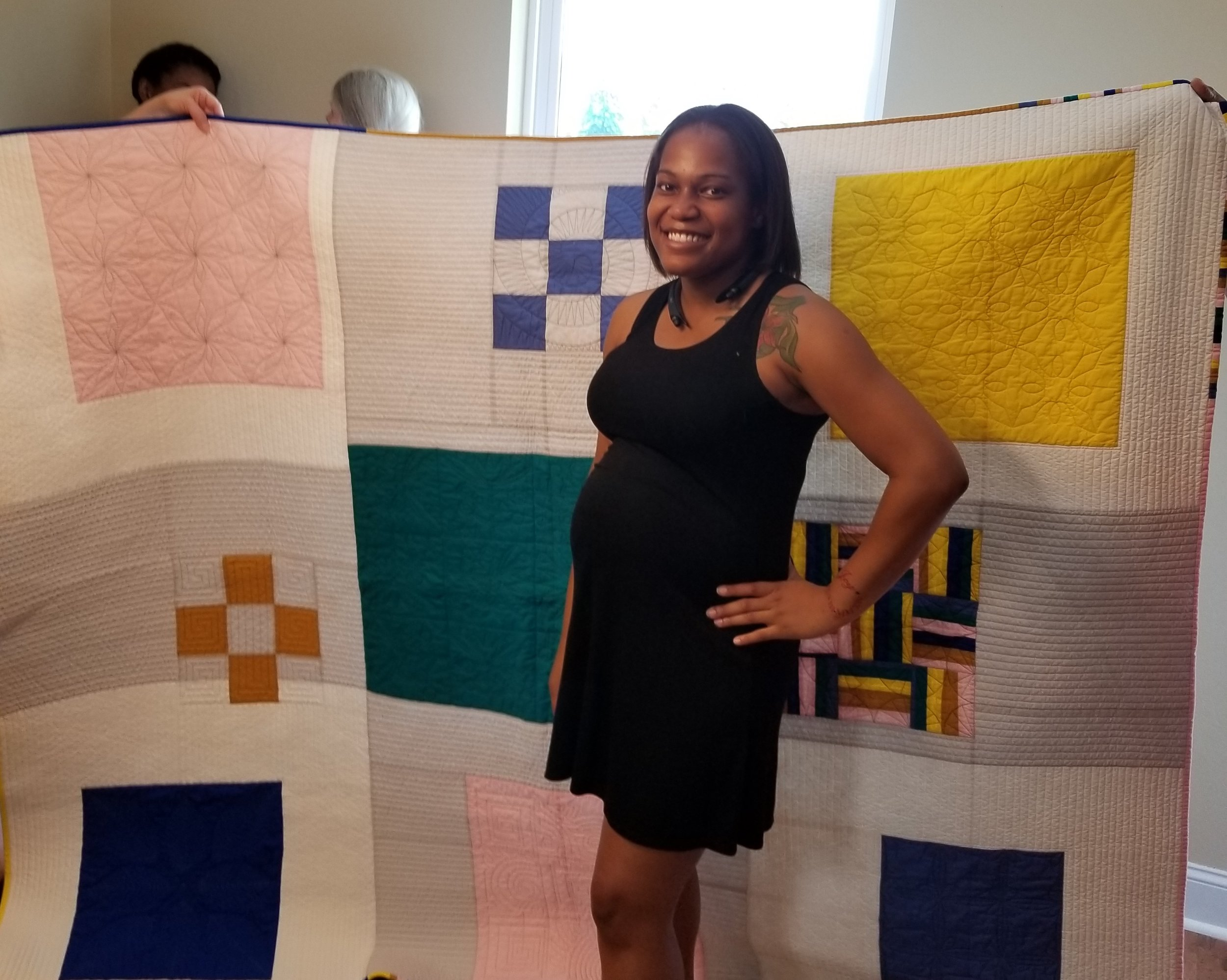 Homeowner Taneshia Hammonds poses with her quilt