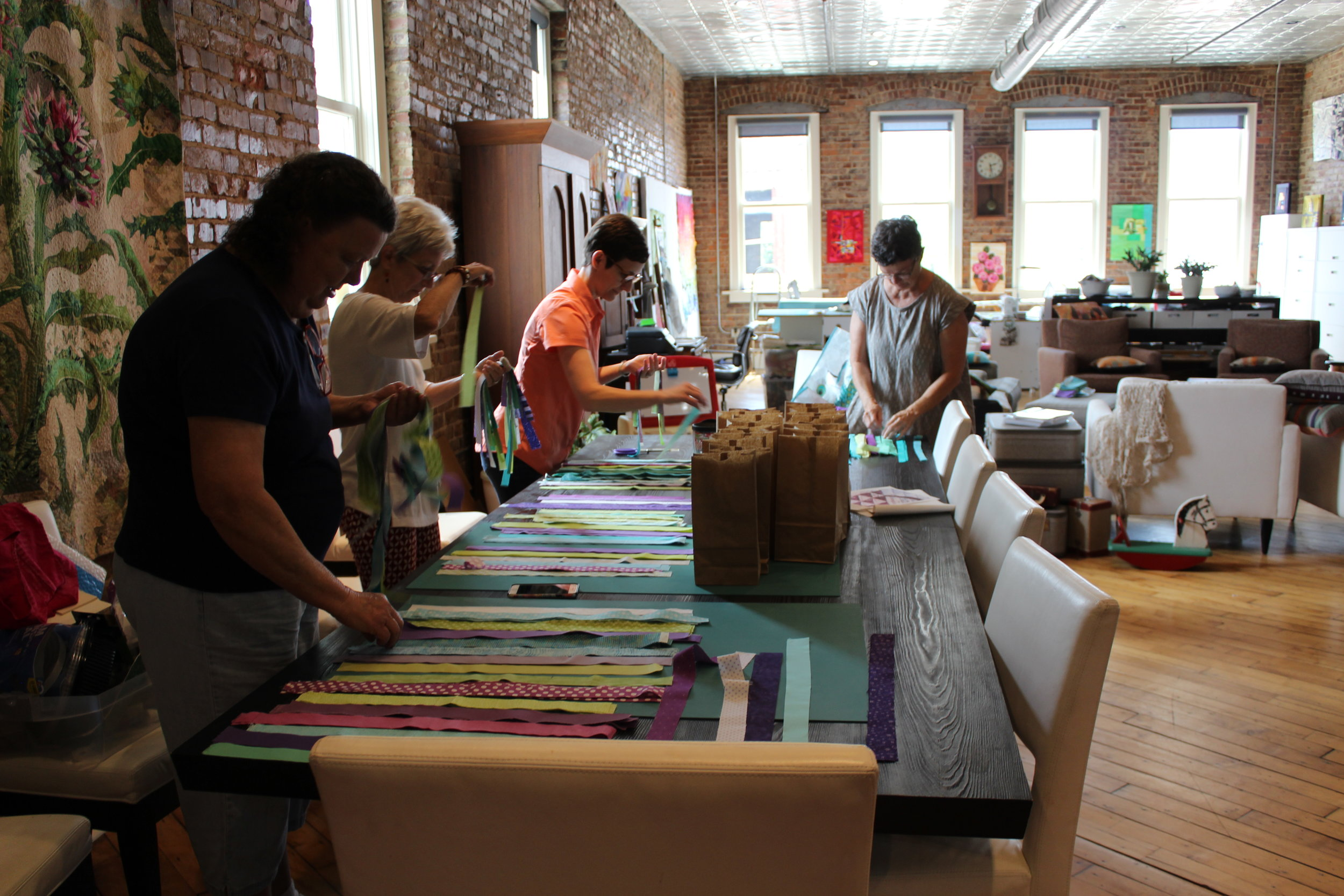 Beverly, Patti Ann, Kelly and Mary sort strips into kits.