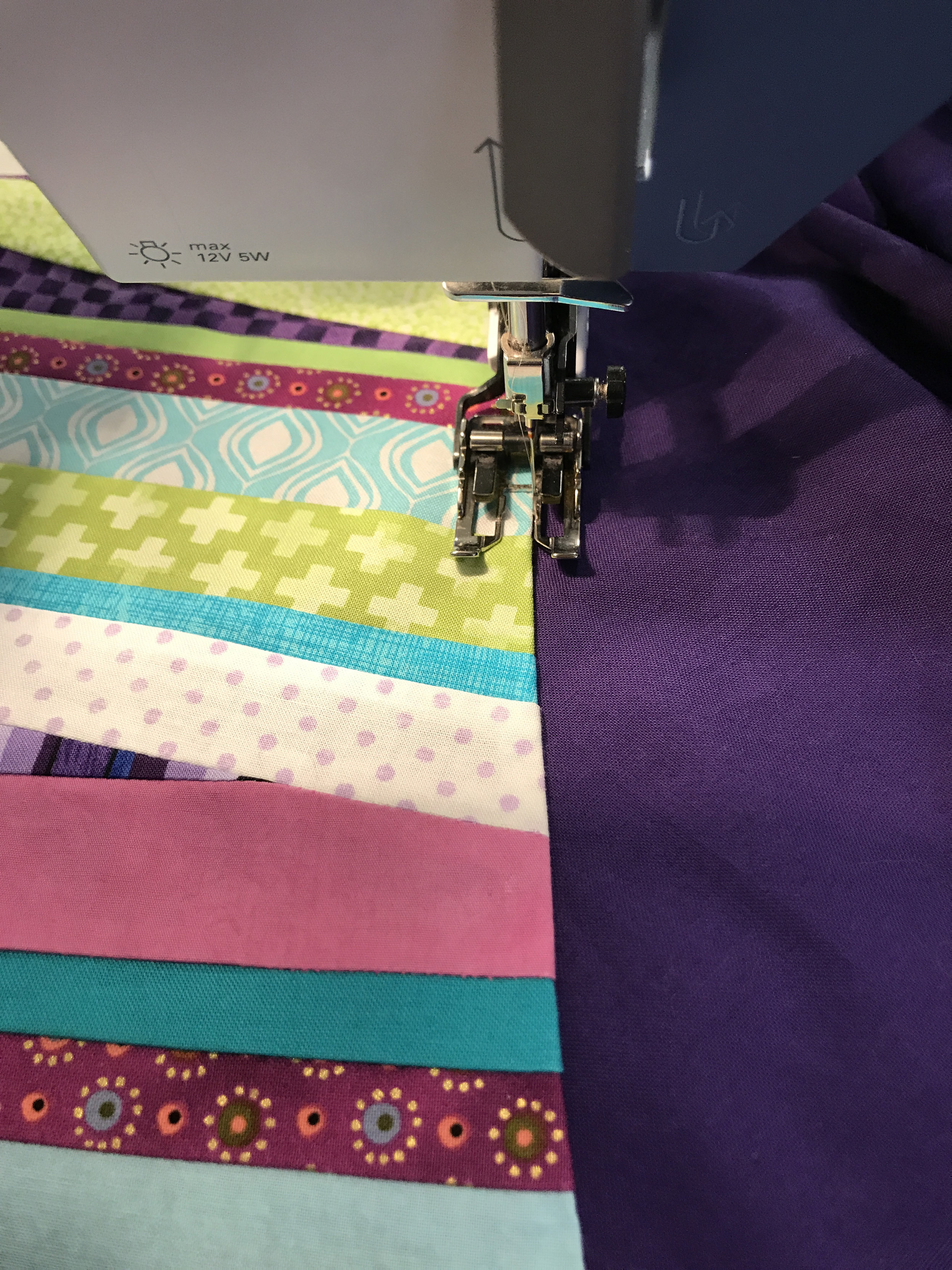 The handle was attached to the quilt top using monofilament thread and machine applique.