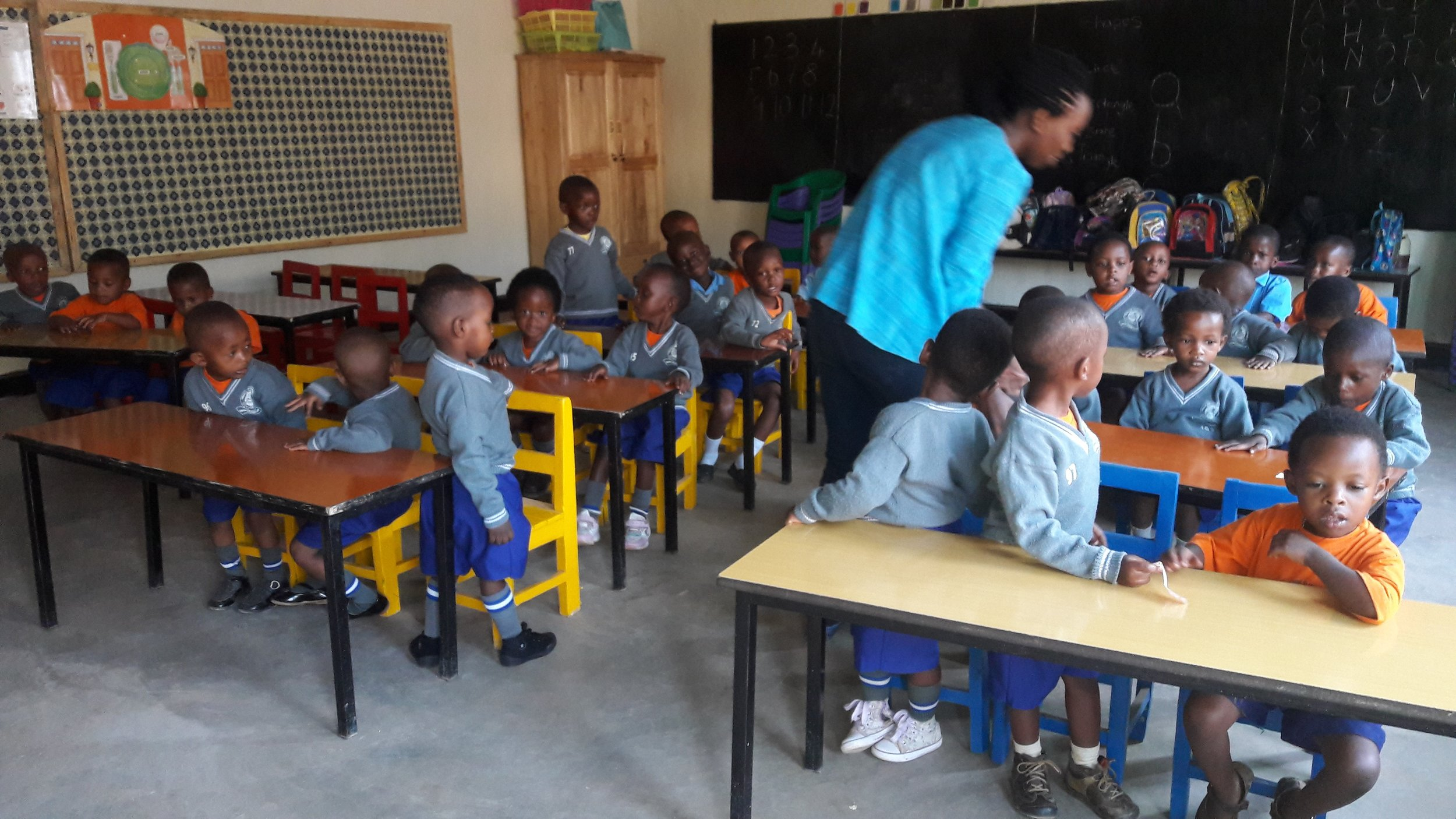 Students in class with chairs, bulletin boards and chairs