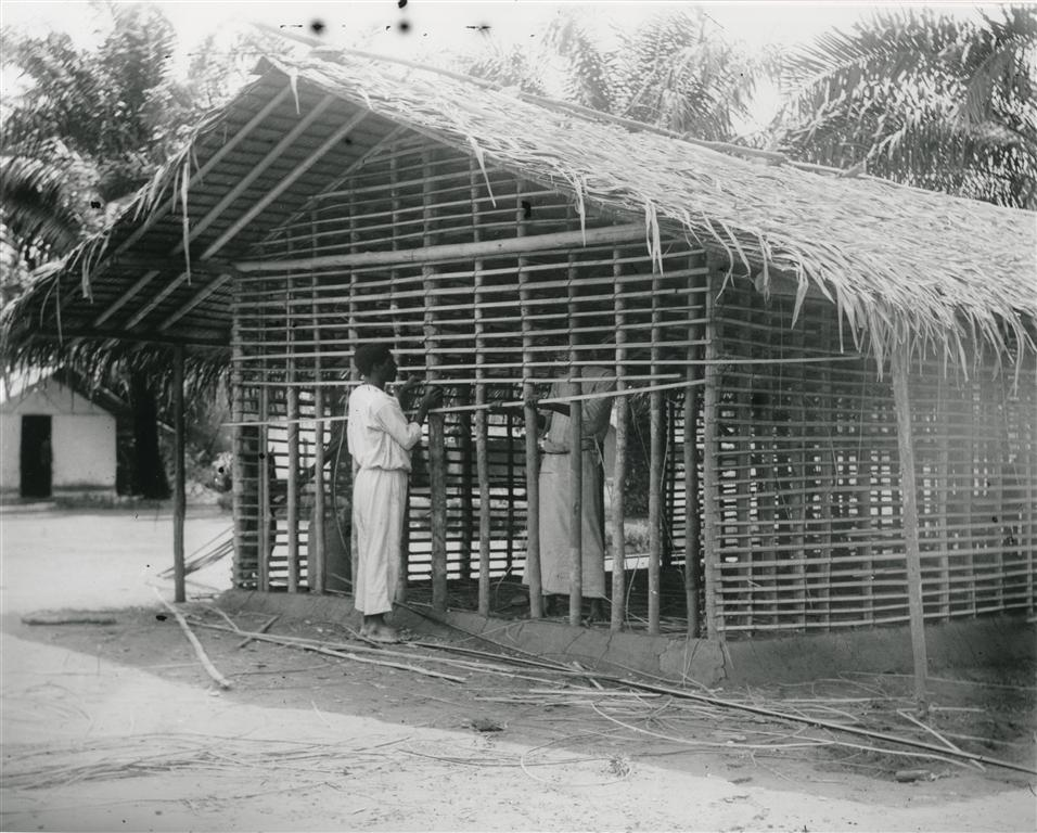 My grandfather Fred founded and operated the Frank James Industrial School. Here two students build a thatch-roof house.