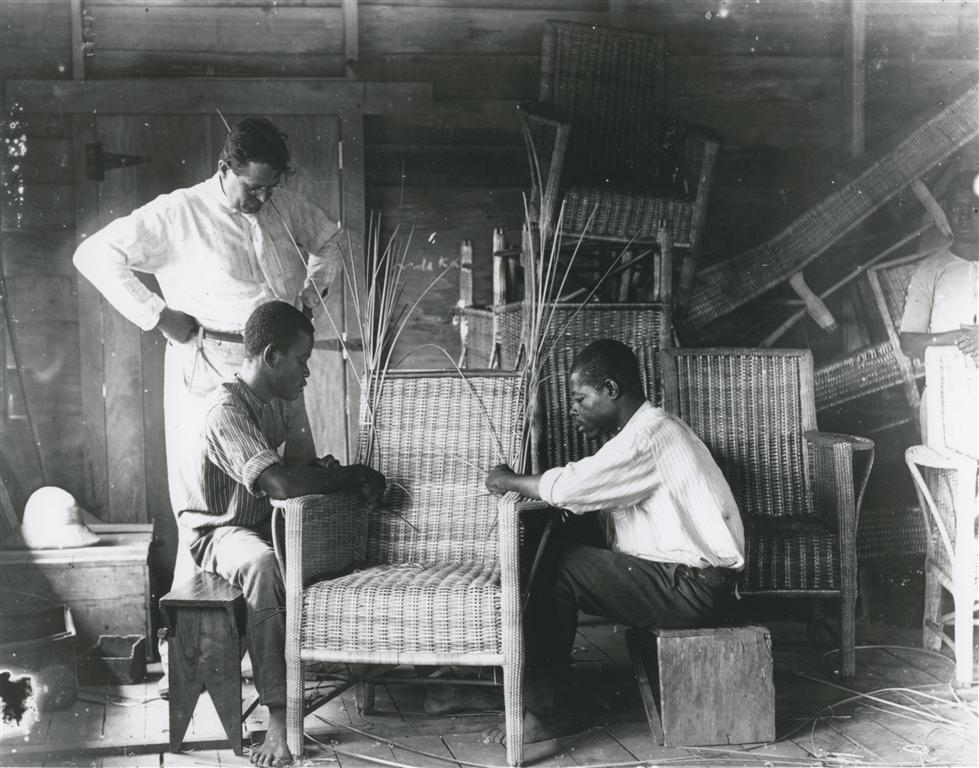 My grandfather and two students in the furniture-making class. On the left you see his pith helmet.