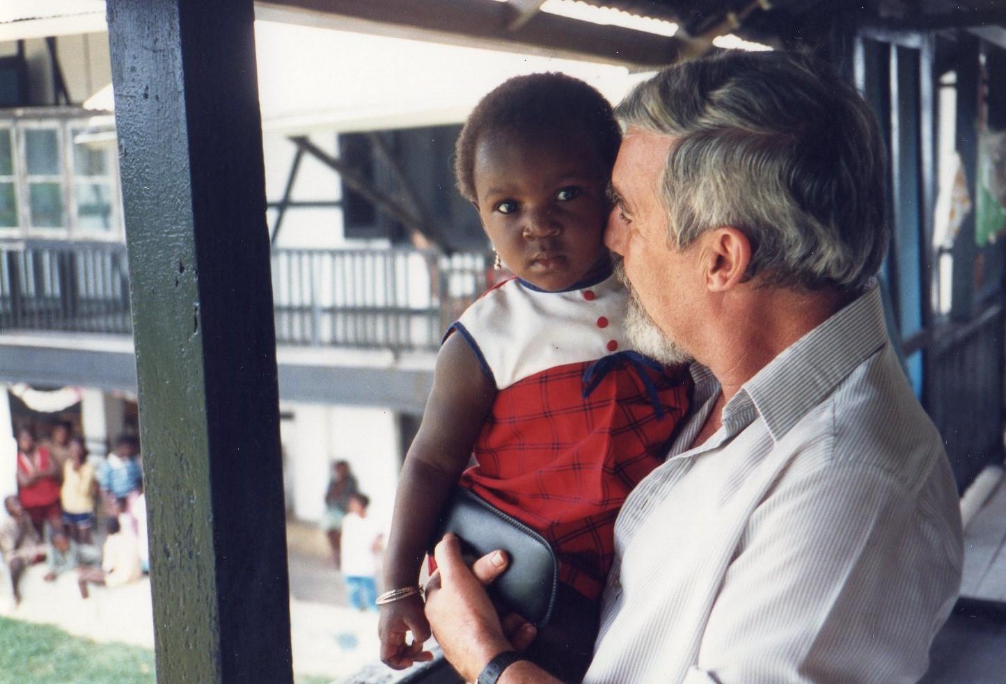 Guy Bekaert, French missionary based in Yaounde, with a child at Sakbayeme orphanage