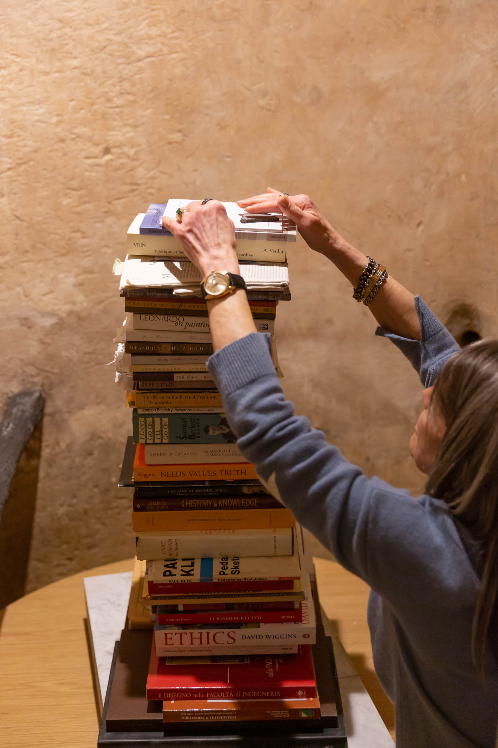 Karshan placing two meteorites at the top of her Tower for L'Aquila - a tower of books comprised of books from her own library and from L'Aquila's library. Photography: Nora Novak.
