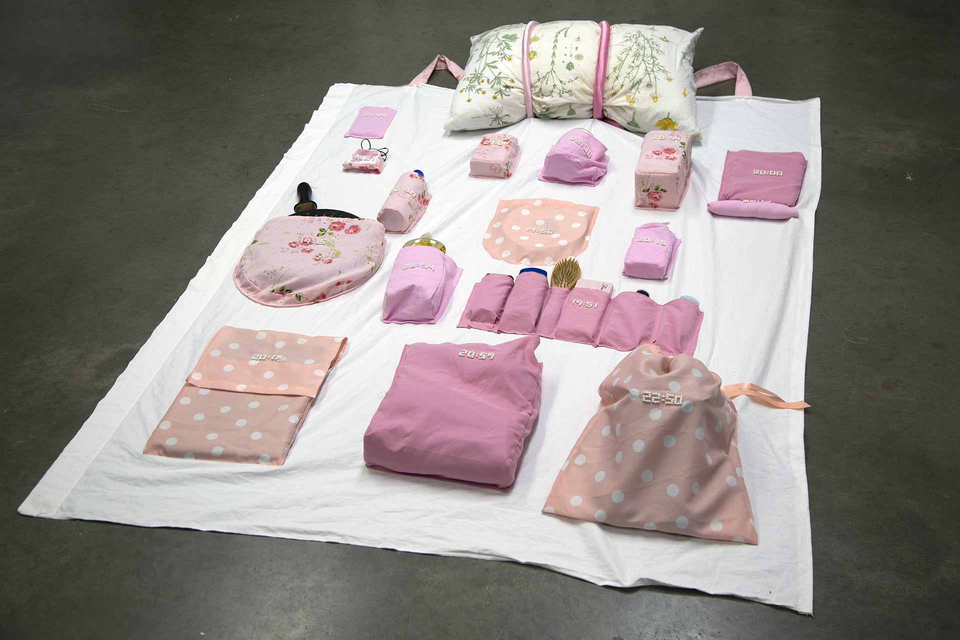 """Tiana Atherton Fibre Structures I , 2018  Concordia University   Encrypted Cloth /  """"Encode"""" two discrete data sets into your project, considering the relationship between them.  Tiana made this mobile """"backpack"""" of all of the objects she uses on a daily basis, things that provide both comfort and stress. Each pocket is embroidered with a time, indicating when she took an anti-anxiety medication."""