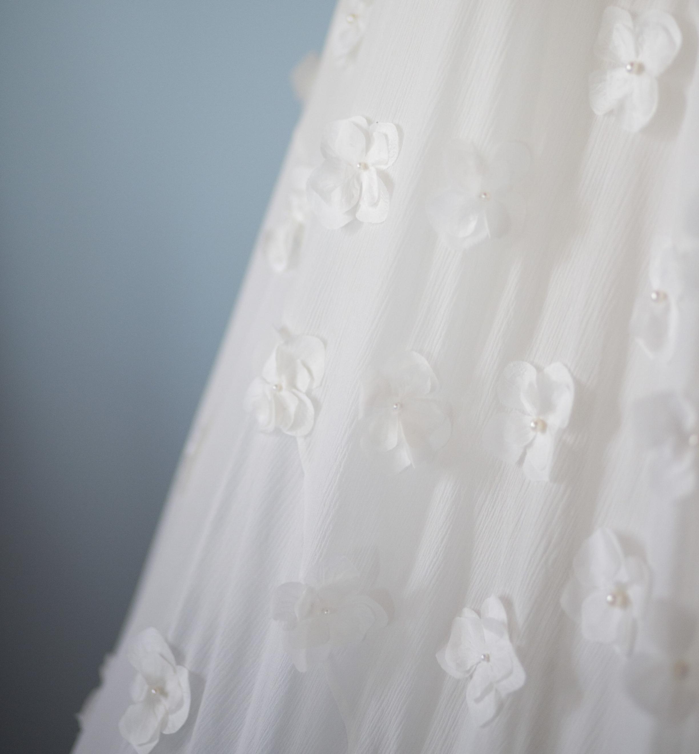 La réalisation de la robe en atelier - Dessin et fiche technique partent ensuite en réalisation dans des ateliers parisiens de prestige choisis avec soin par Camille. Travaillant au quotidien pour des marques de renom, leur savoir-faire incomparable est sublimé par l'utilisation de matières nobles et de qualité supérieure fabriquées en France, à l'instar des incontournables dentelles Soltiss et Sophie Hallette.Encadrés par la créatrice qui souhaite être au plus près du processus de production, les ateliers font de chaque robe une véritable création Haute Couture confectionnée avec patience et délicatesse.