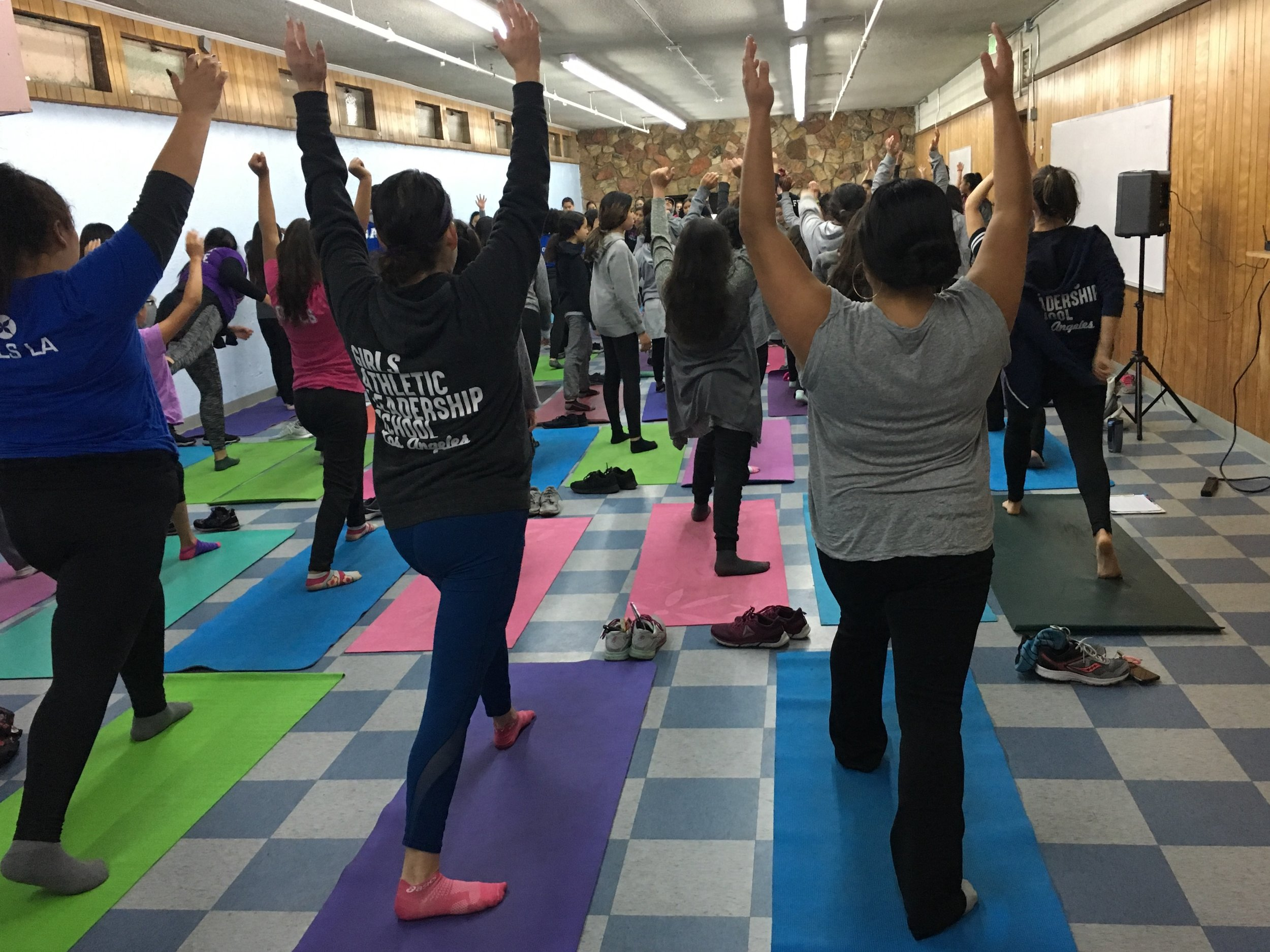 Jazmin and Vanessa Garza, founding principal of Girls Athletic Leadership School, doing yoga with her middle school students and staff.
