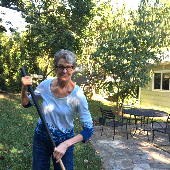 Kate rakes leaves in the yard of the home she has lived in for more than three decades.