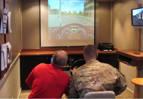 America's Road Team Captain Gives a Soldier Stationed at Fort Benning a Sample of Training Technology Drivers-in-Training Might Use During Their Apprenticeship.