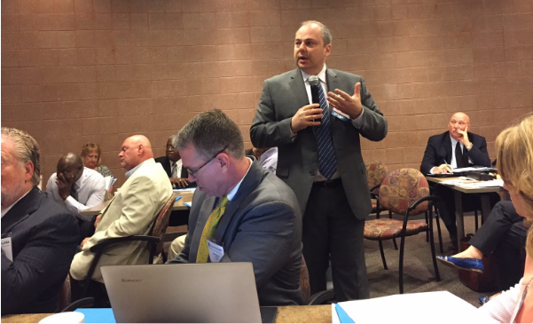 John Ladd, Administrator, Office of Apprenticeship, U.S. Department of Labor (standing) gives information on the economic benefits of the Registered Apprenticeship Program.