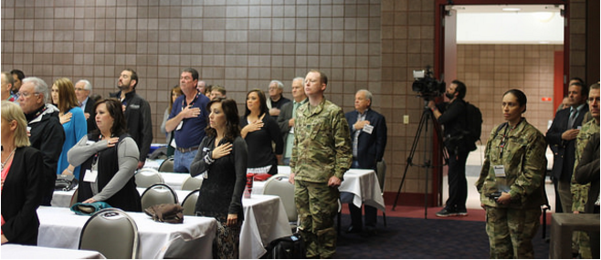 Employers and Active-Duty Service Members Stand for the National Anthem during ESGR signing ceremony sung by Ms. Janine Stange.